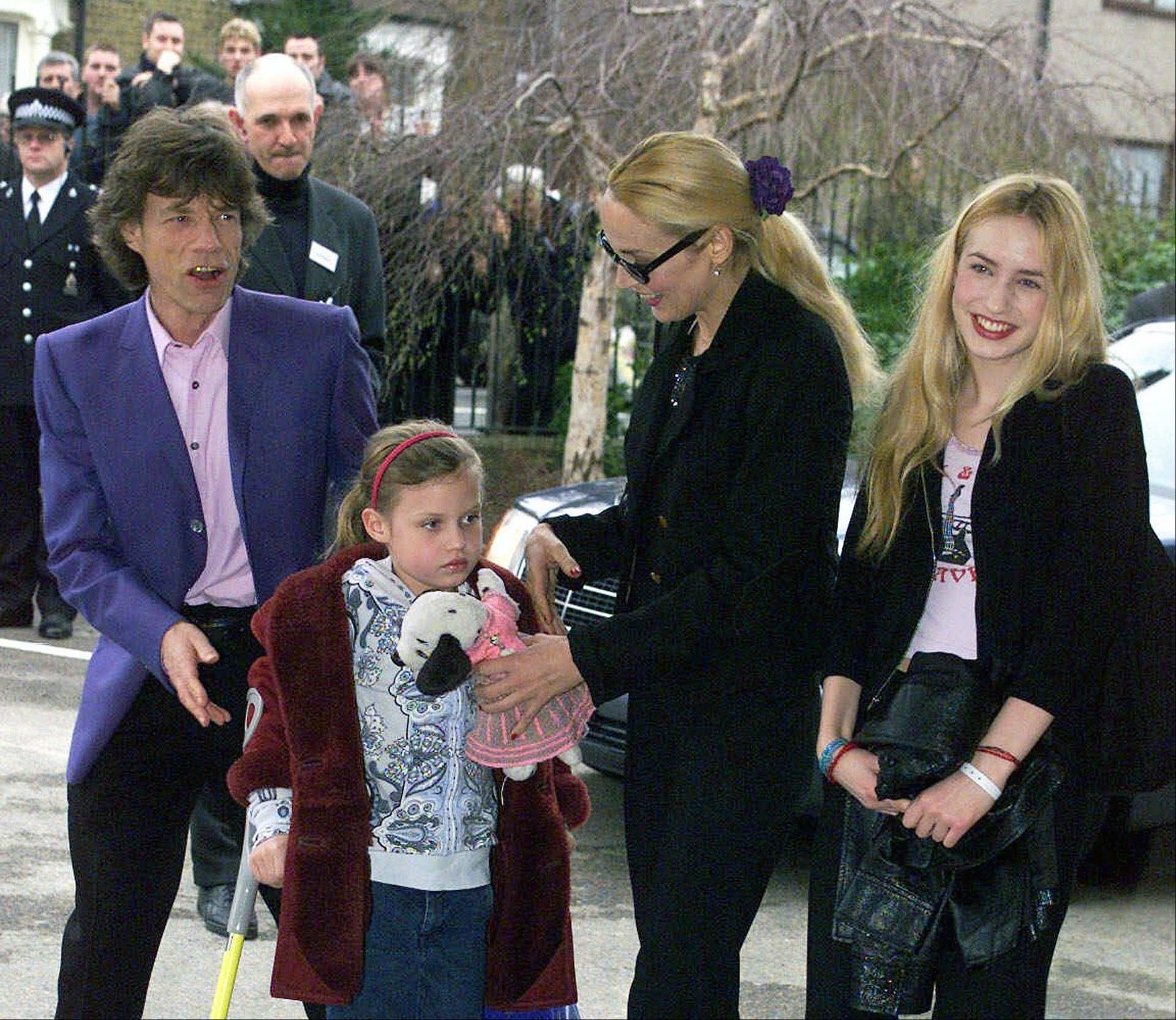El 20 de marzo de 2000, Mick Jagger llega a su antigua escuela en Dartford, al este de Londres, para abrir un nuevo centro de música con su ex esposa Jerry y sus hijos, Elizabet y Georgia.