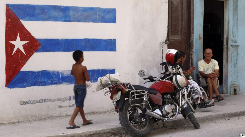 Un niño pasa junto a una pintura de la bandera cubana en una pared, en La Habana, Cuba (Foto: Martí Noticias)
