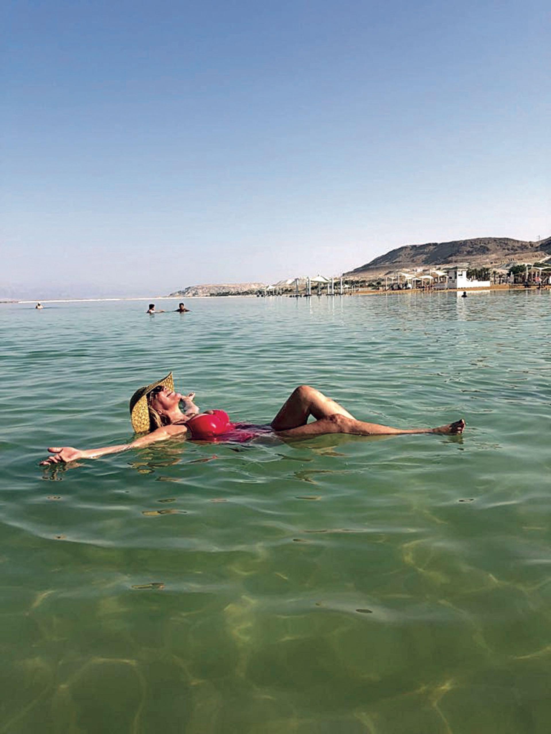 """Flotando en el Mar Muerto, entre Jordania e Israel, """"donde el agua es híper salina sana""""."""