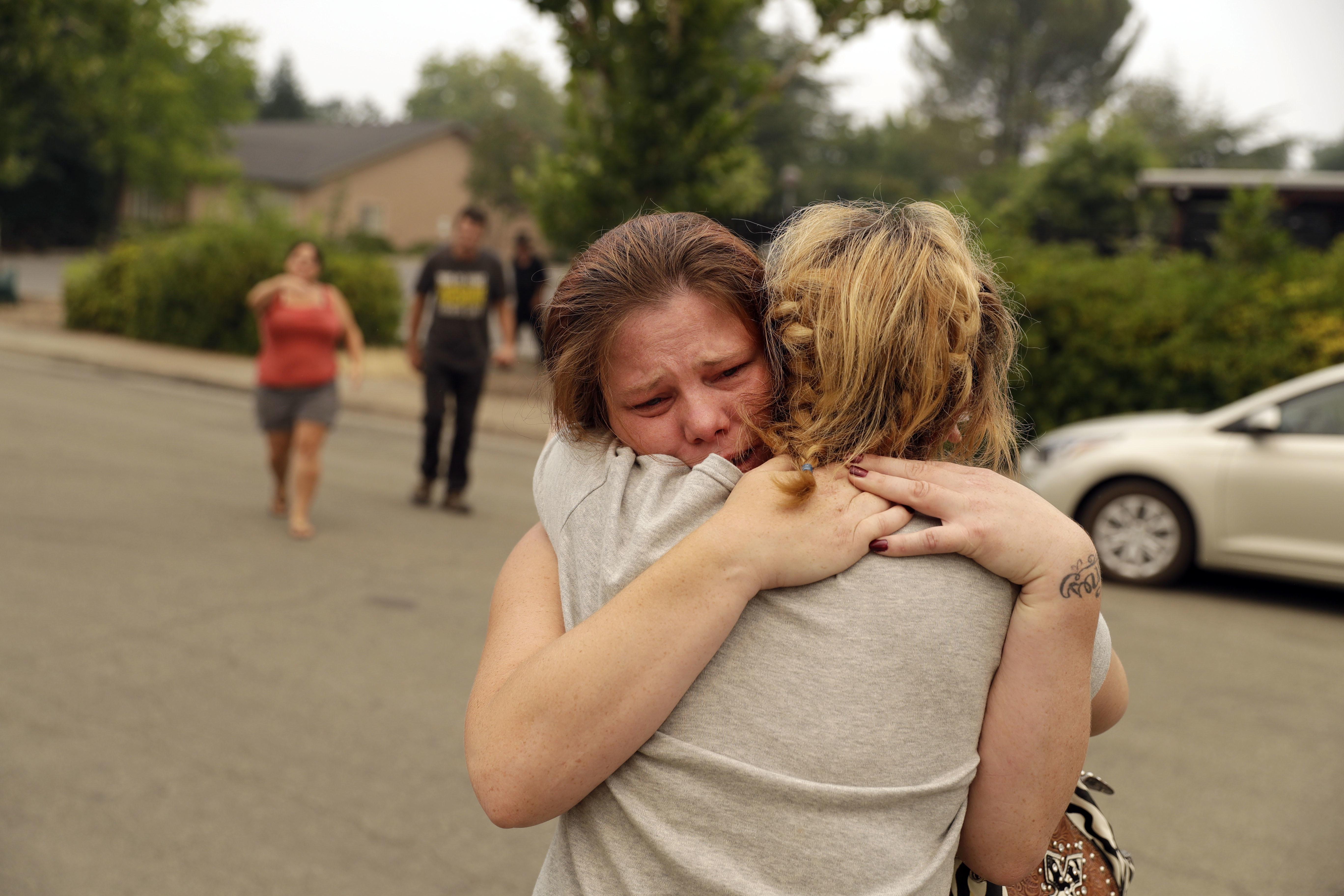 Carla Bledsoeabraza su hermana Sherrytras enterarse que los hijos de Sherry,James y Emily,murieron junto con la abuela durante el incendio el sábado (AP/ Marcio Jose Sanchez)