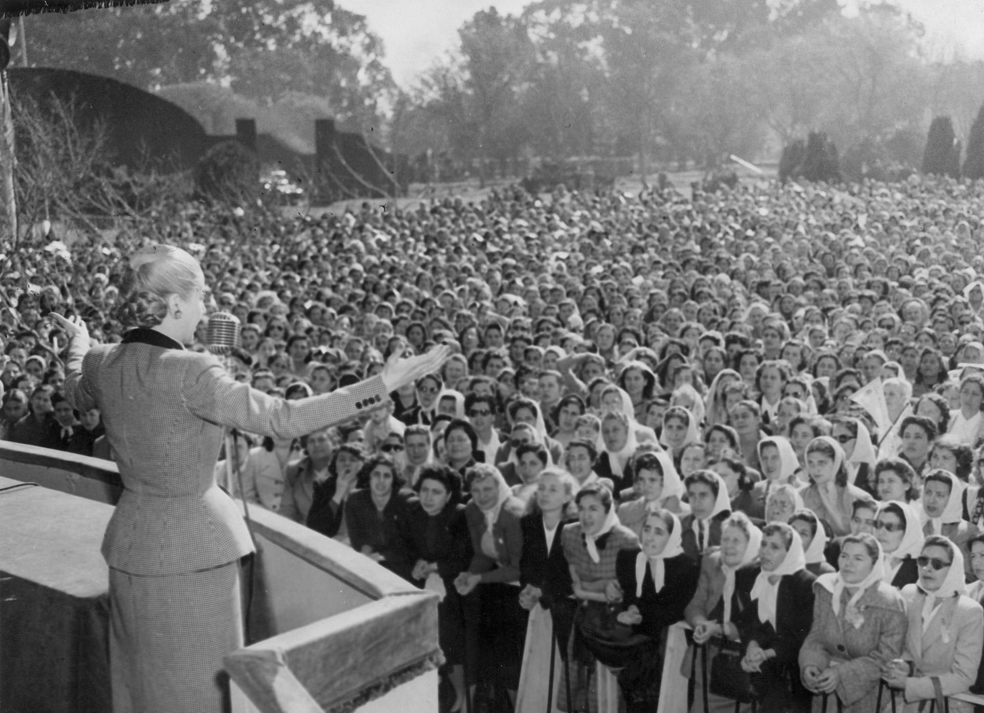 """El 21 de agosto de 1946 el proyecto del voto femenino es aprobado por la Cámara de Senadores, para que el 9 de septiembre del año siguiente hiciera lo propio la Cámara de Diputados. Días más tarde, el 23 de septiembre de 1947, se promulga finalmente la Ley 13.010. Evita es una férrea impulsora de la norma. Ese día, ante una Plaza de Mayo atestada de mujeres, pronuncia uno de sus discursos más emblemáticos: """"Recibo en este instante de manos del Gobierno de la Nación la ley que consagra nuestros derechos cívicos. Y la recibo, ante vosotras, con la certeza que lo hago en nombre y representación de todas las mujeres argentinas, sintiendo jubilosamente que me tiemblan las manos al contacto del laurel que proclama la victoria"""" (Getty Images)"""
