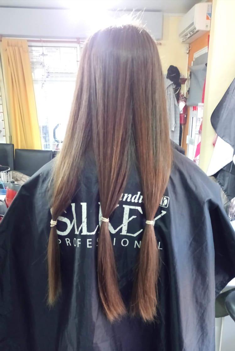 Una vez que la clienta se decide por cortar el pelo, con banditas marca la cantidad y el largo.