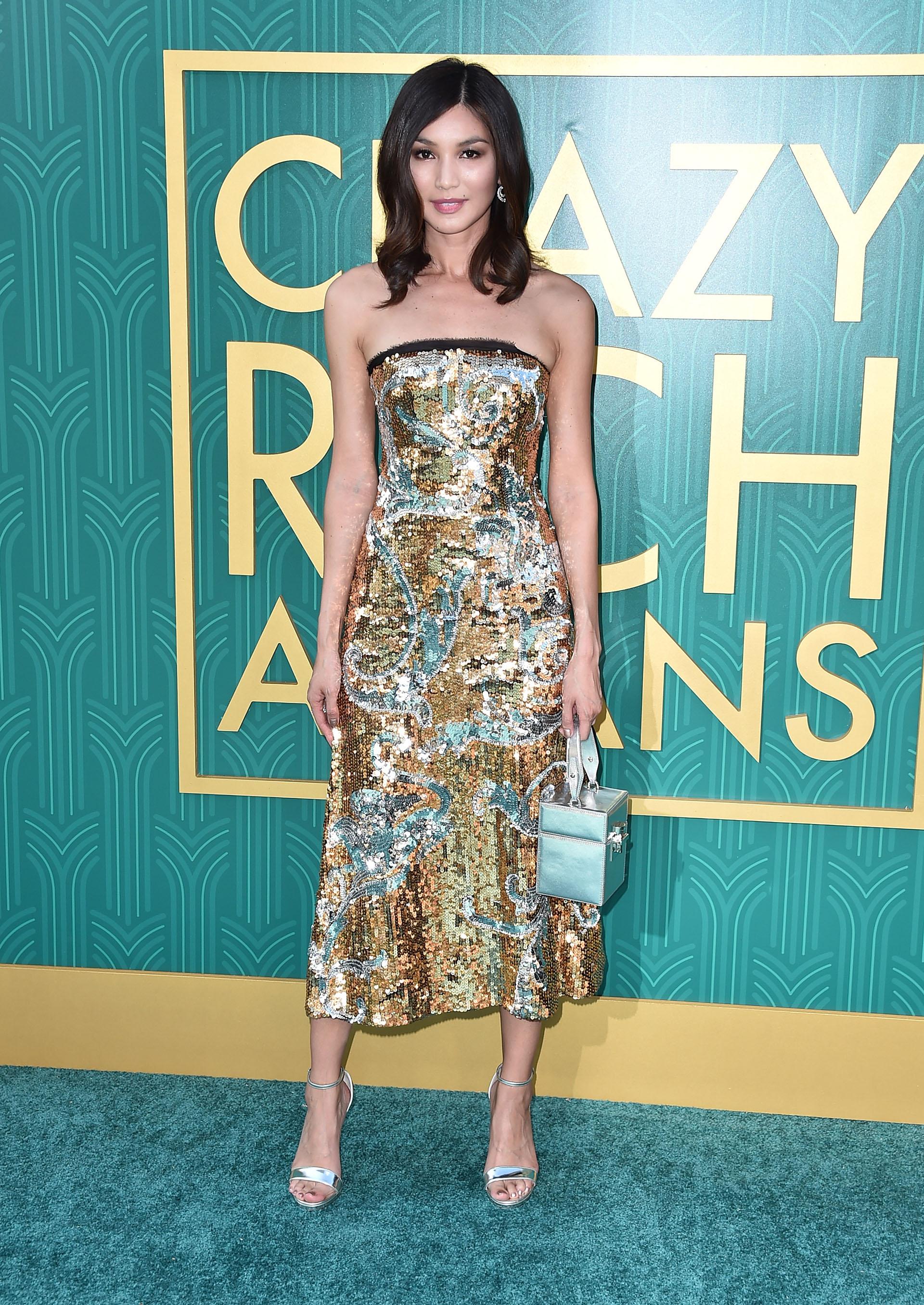 Gemma Chan cautivó con este diseño metálico de lentejuelas y un bolso de mano estilo baúl