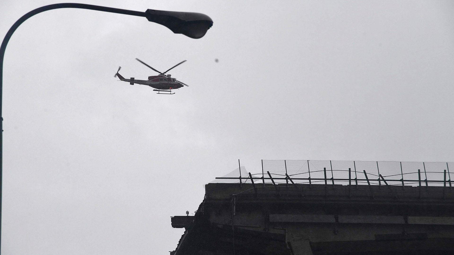 Un helicóptero sobrevuela la sección del viaducto sobre la autopista A10 que se desplomó en Génova (EFE)