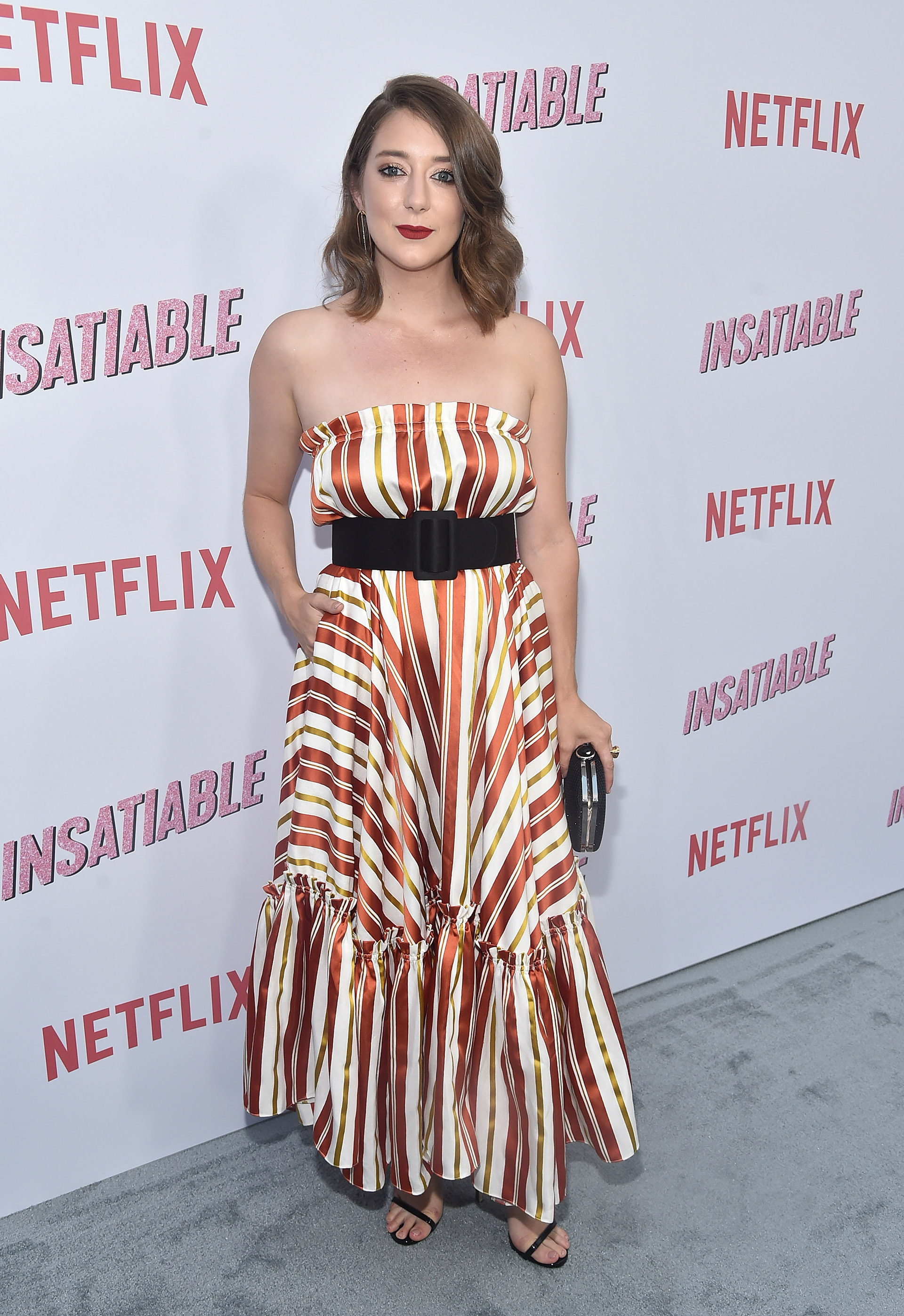 Kimmy Shields con un colorido vestido a rayas y volado en la falda