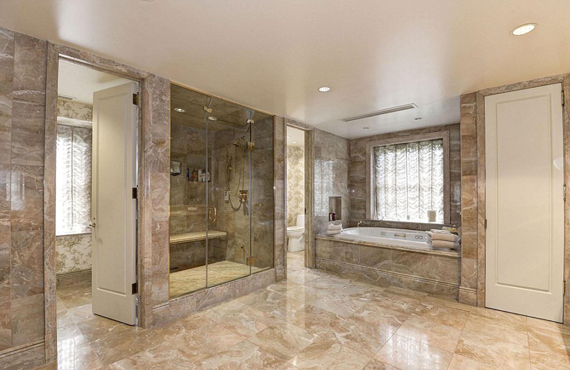 El imponente baño con una bañera, una ducha y un pequeño Spa en la que predomina el marmol