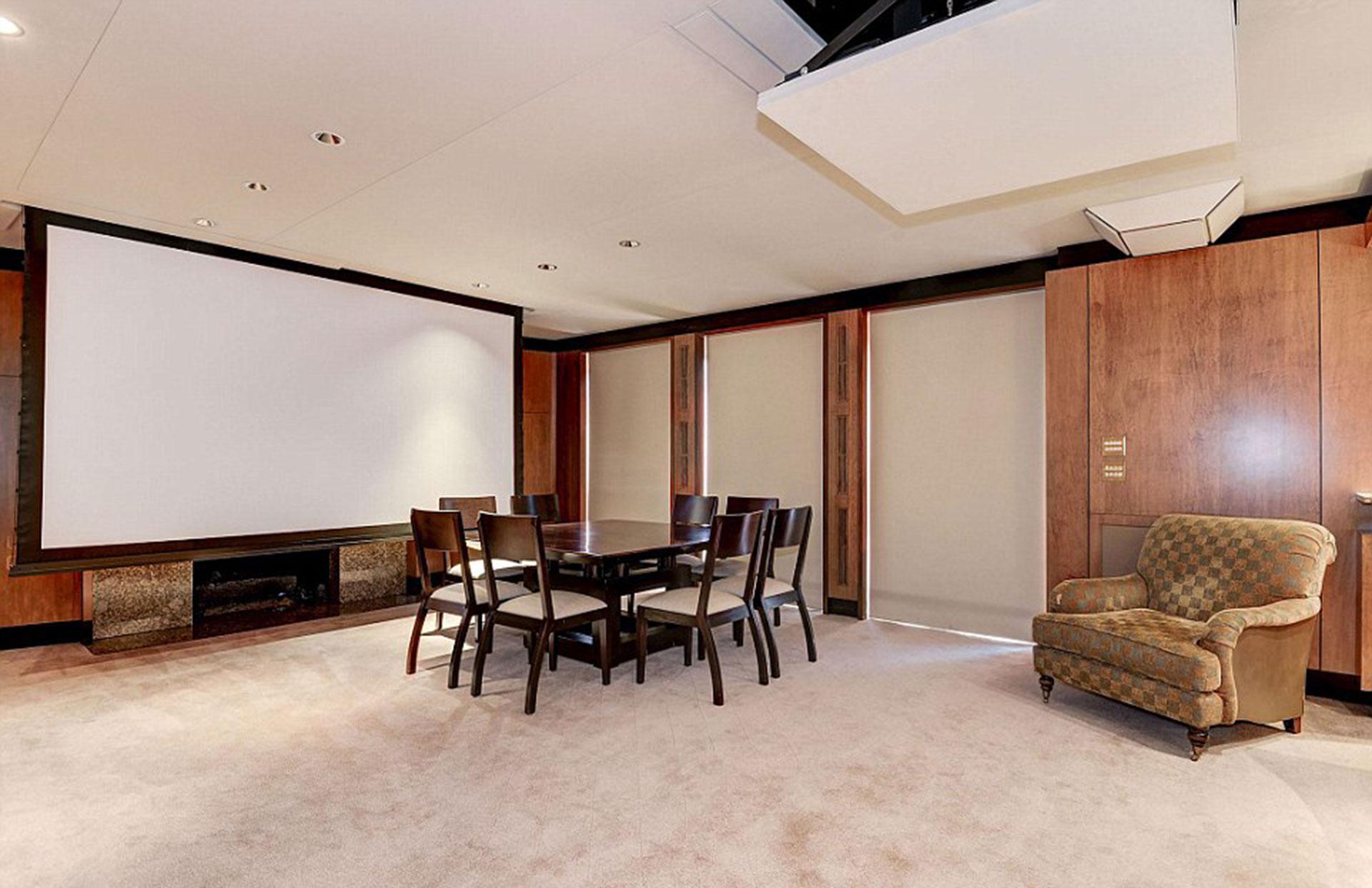 Una pantalla gigante y una mesa de reuniones en la misma habitación