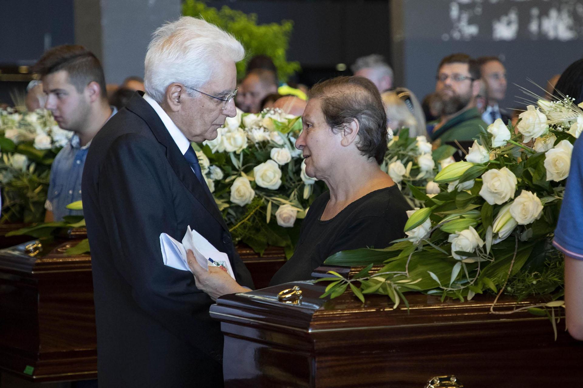 El presidente Sergio Mattarella conversa con una familiar de una víctima. EFE