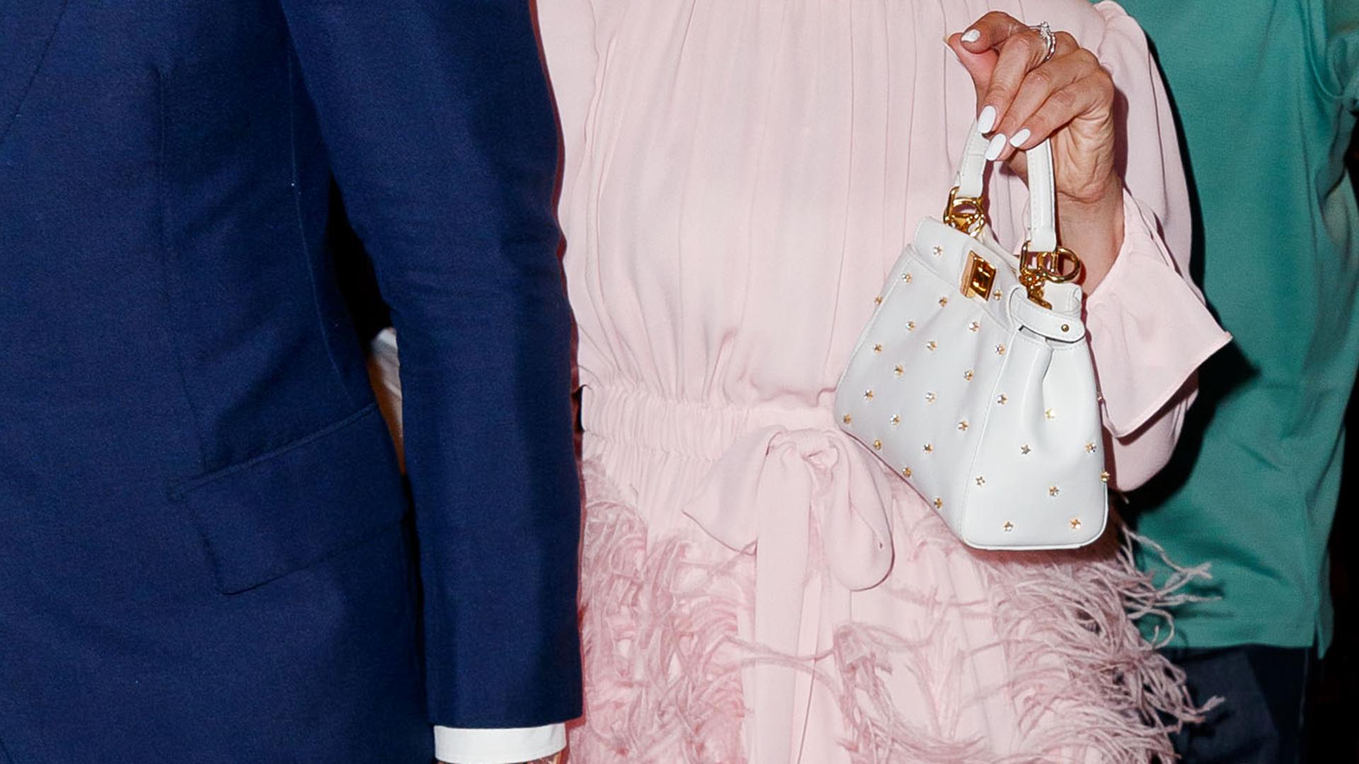 El detalle de su pequeña cartera de mano blanca, con detalles oro