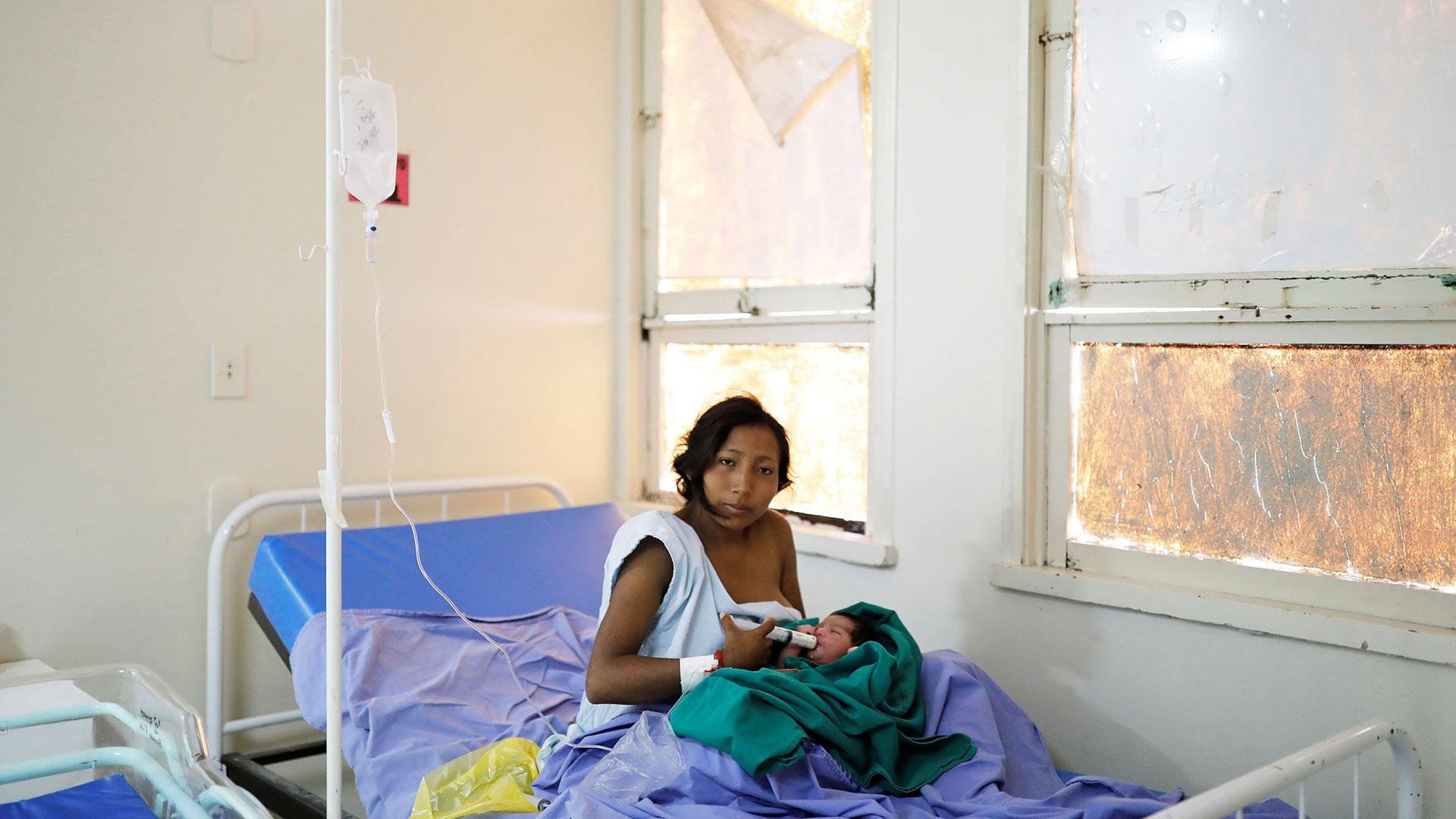 María Teresa López, de 20 años, indígena Warao del estado de Delta Amacuro, usa una jeringa para alimentar a su bebé Fabiola, de un día, en una maternidad en Boa Vista, estado de Roraima, Brasil, el 21 de agosto de 2018.(Reuters)