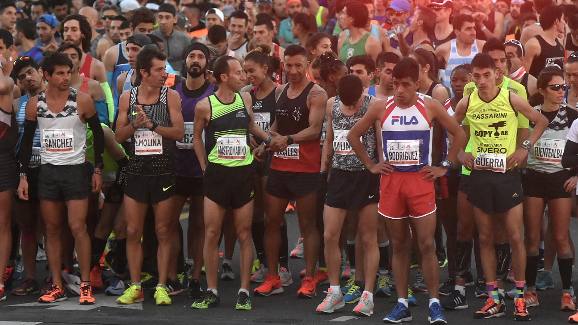 Los atletas, luego de elongar, se ubican detrás de la línea de partida. Los atletas generales se posicionan detrás de los atletas de élite