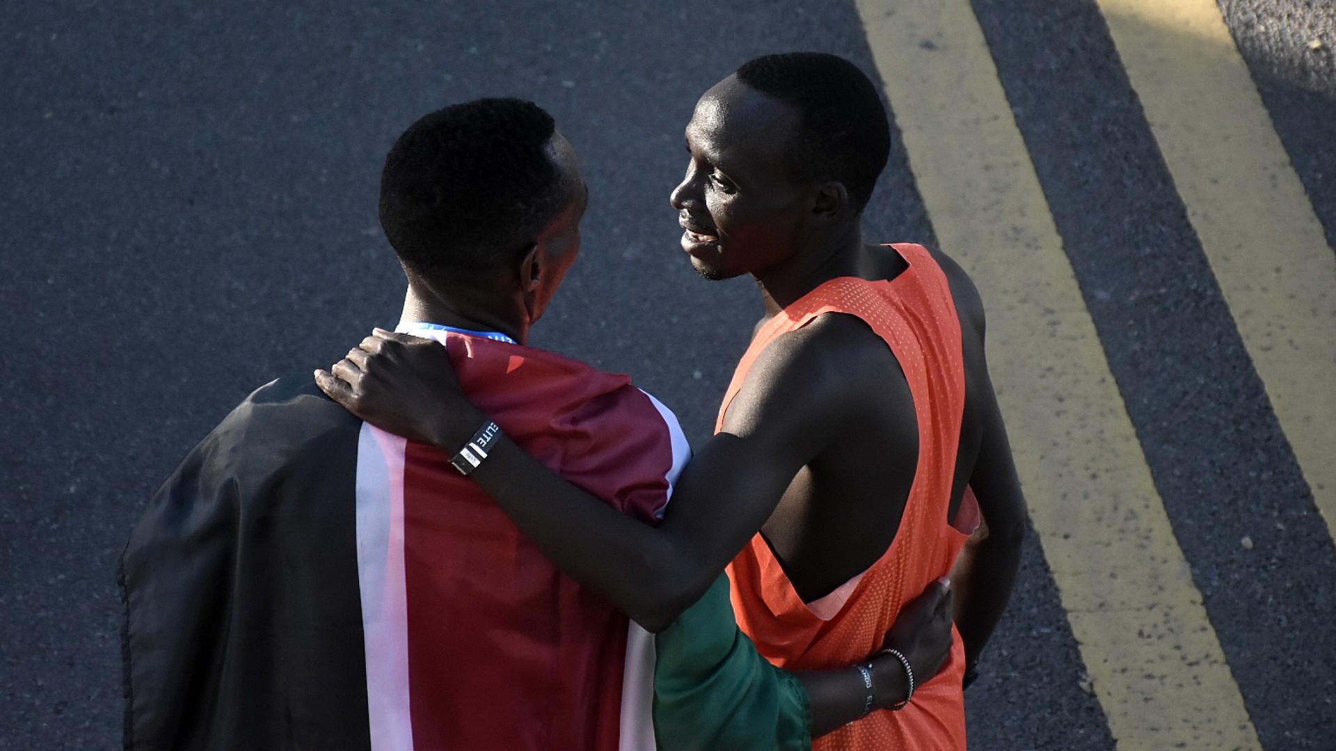 Cherono y Keroki se abrazan. Keroki, en segundo lugar, con una bandera al hombro