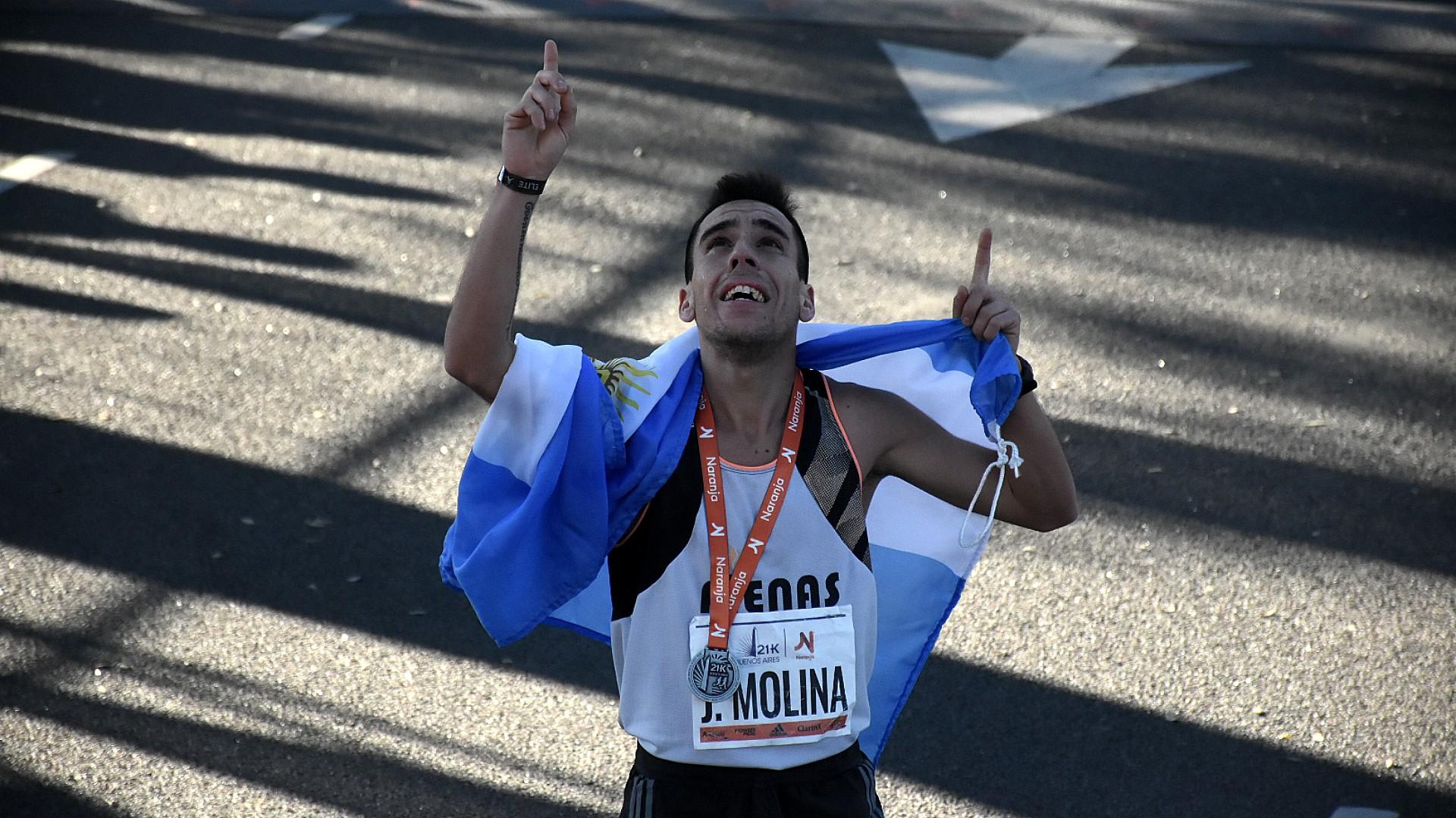 Julián Molina fue el primer argentino en llegar, con 1:04:19. Festeja su victoria con la bandera argentina