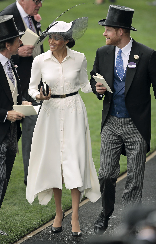 Más que una lady, Meghan Markle deslumbró el 19 de junio en Berkshire. El día de su debut en el hipódromo para ver las carreras del Royal Ascot, llevó un vestido camisero con falda corte pañuelo y flores bordadas en la cintura de Givenchy. Un cinturón negro finito funcionó de corte, combinado con zapatos negros Balenciaga y un clutch también de Givenchy. El tocado en blanco y negro de Philip Treacy equilibró el look. Así como los aros con forma de pétalo de oro y diamantes pétalo by Birks. (AFP PHOTO / Daniel LEAL-OLIVAS)