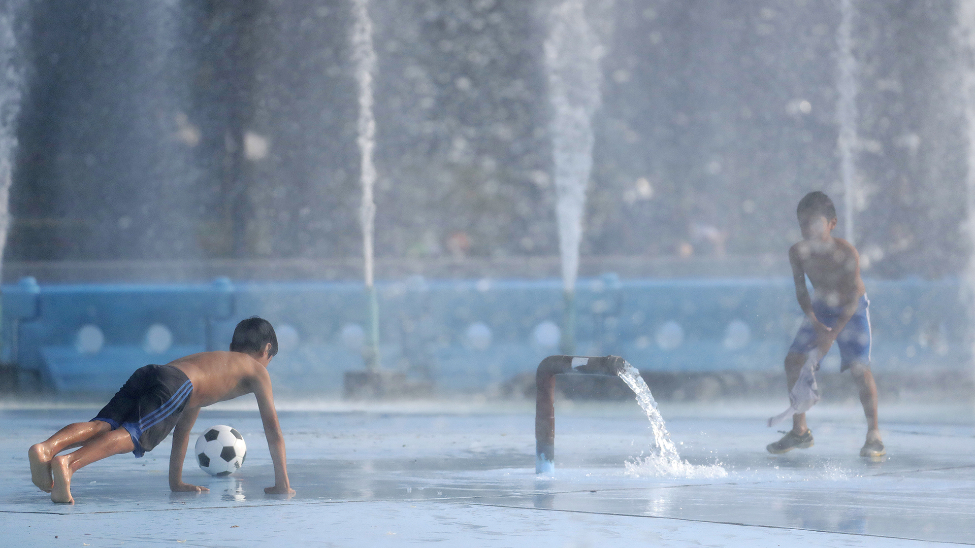 Los chicos combaten el calor jugando en el agua del Billie Jean King National Tennis Center