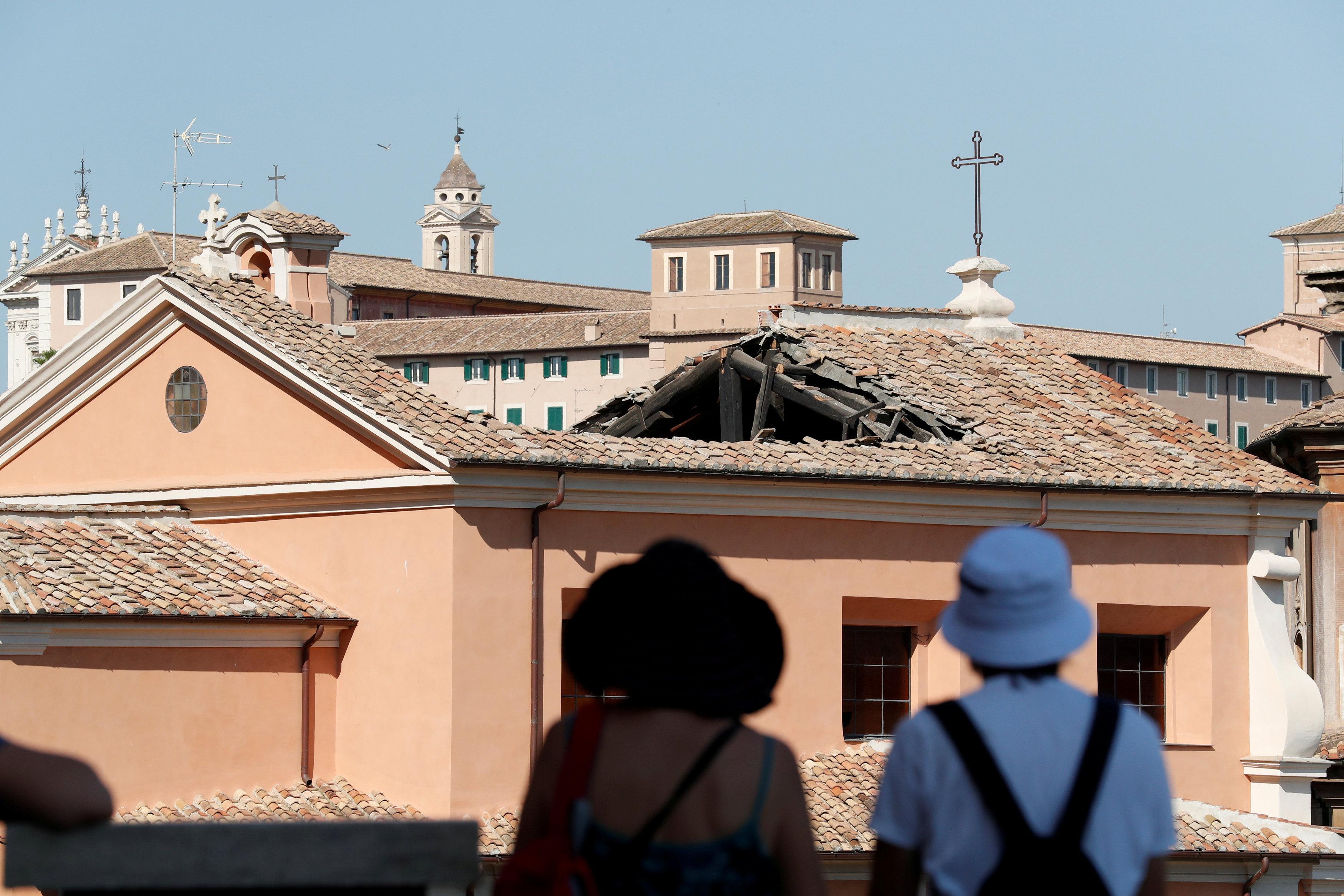 Dos personas observan el techo colapsado de la iglesia de San José de los Carpinteros (REUTERS/Alessandro Bianchi)