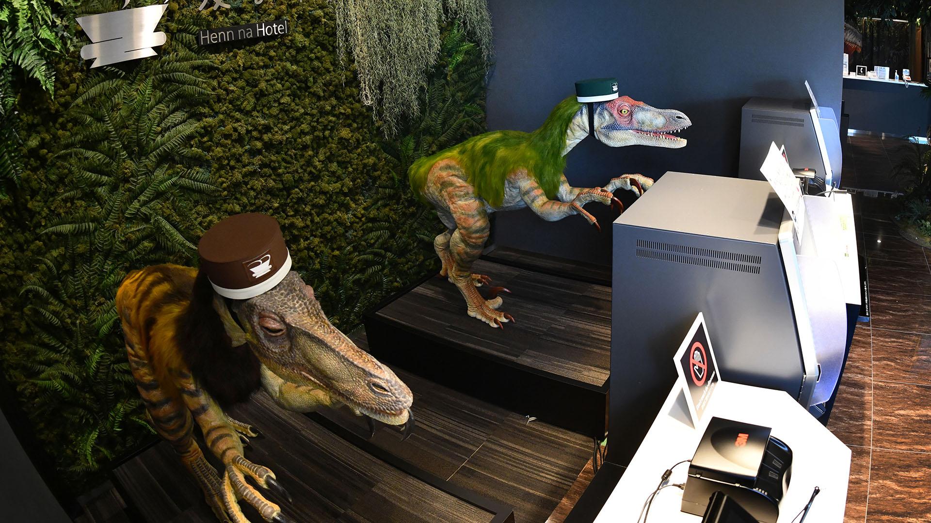 Un par de dinosaurios robot con sombreros de botones reciben a los invitados en la recepción del hotel (AFP PHOTO / Kazuhiro NOGI)