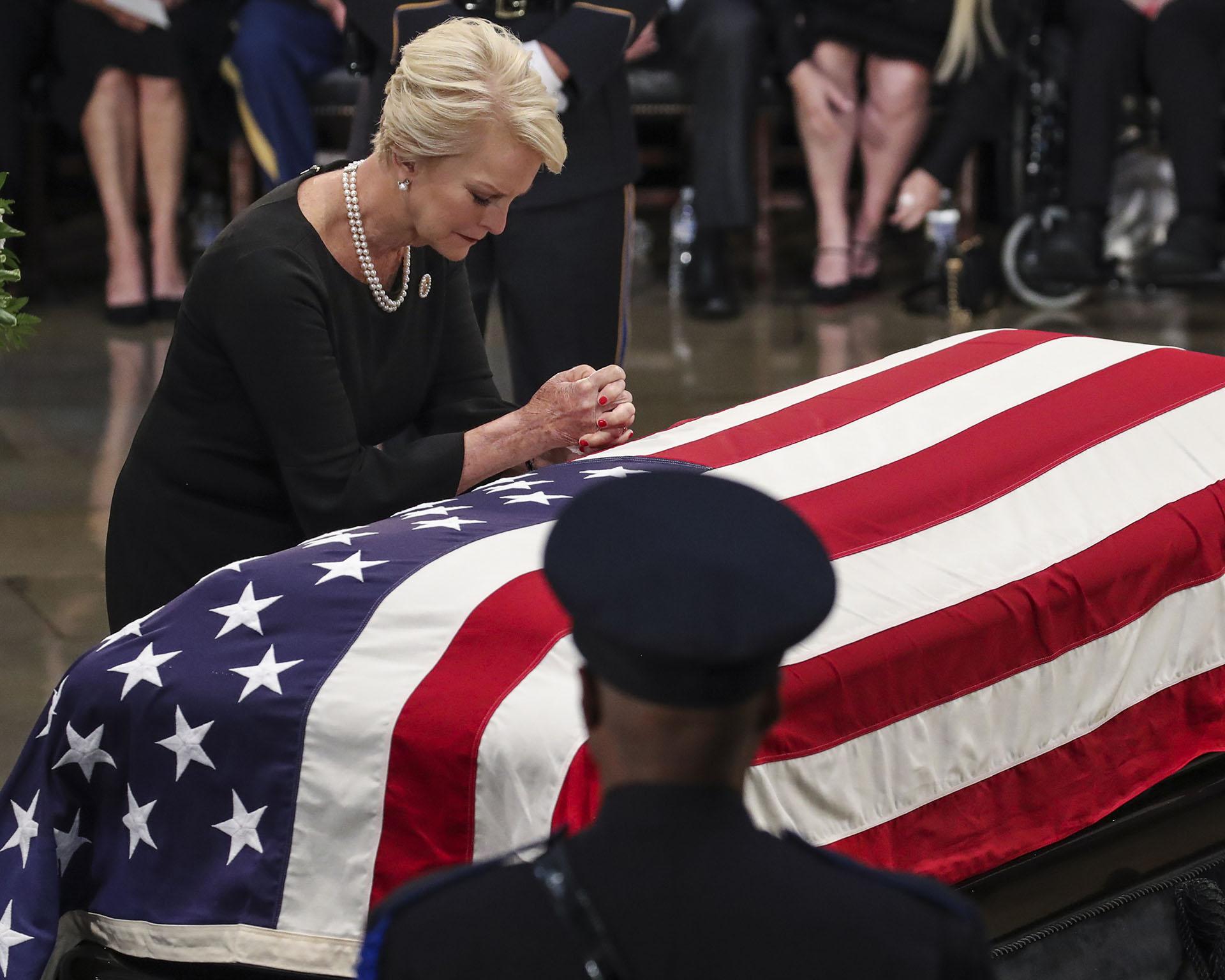 Cindy McCain, viuda del senador John McCain, se apoya sobre el féretro que contiene los restos de su marido, durante el funeral realizado en el Capitolio de Estados Unidos el 31 de agosto (Drew Angerer/Getty Images/AFP)