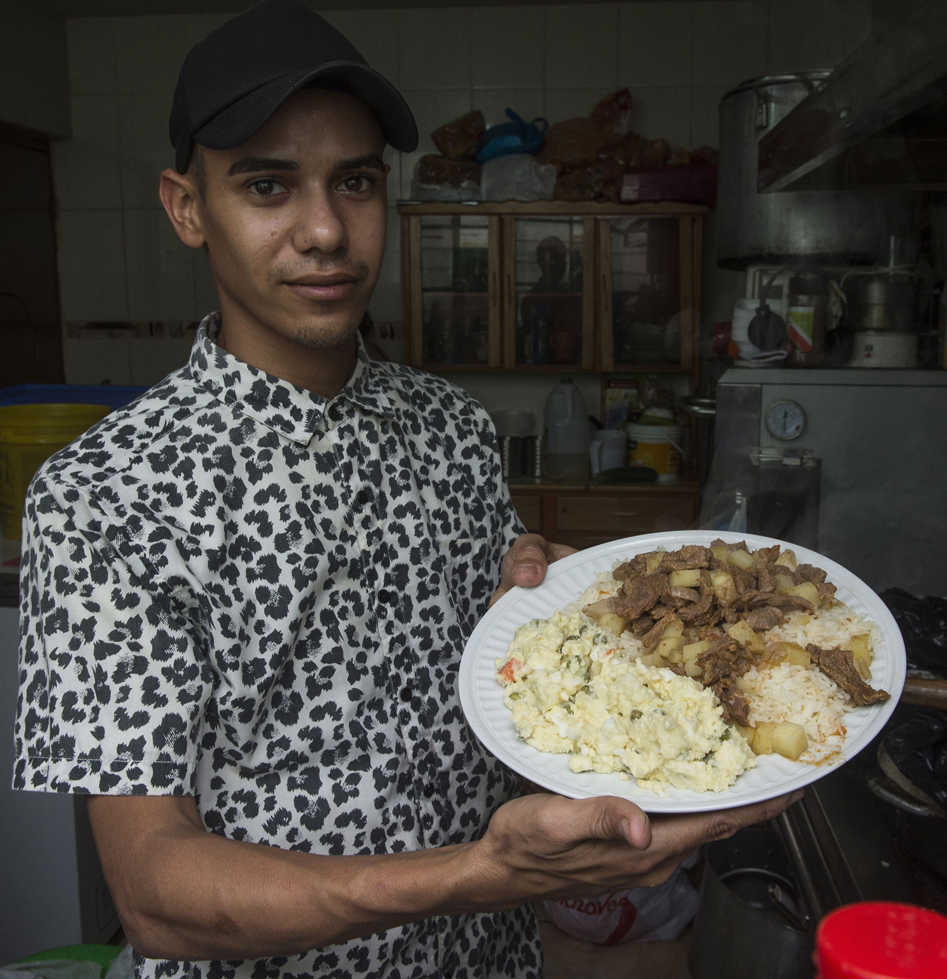 """El cocinero es el venezolano Brean Villegas, de 22 años, a quien lo tiene sin cuidado el llamado del presidente Nicolás Maduro para que los emigrados dejen de lavar """"pocetas"""" (retretes) y vuelvan a Venezuela"""