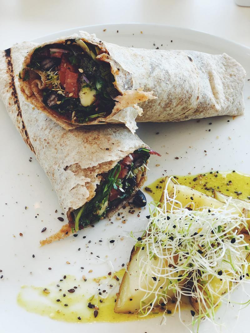 """El wrap de """"Soy Avatar"""", con mix de verdes, frijoles negros, brotes, queso, cilantro, tomates secos y mayonesa de pimientos ahumados."""