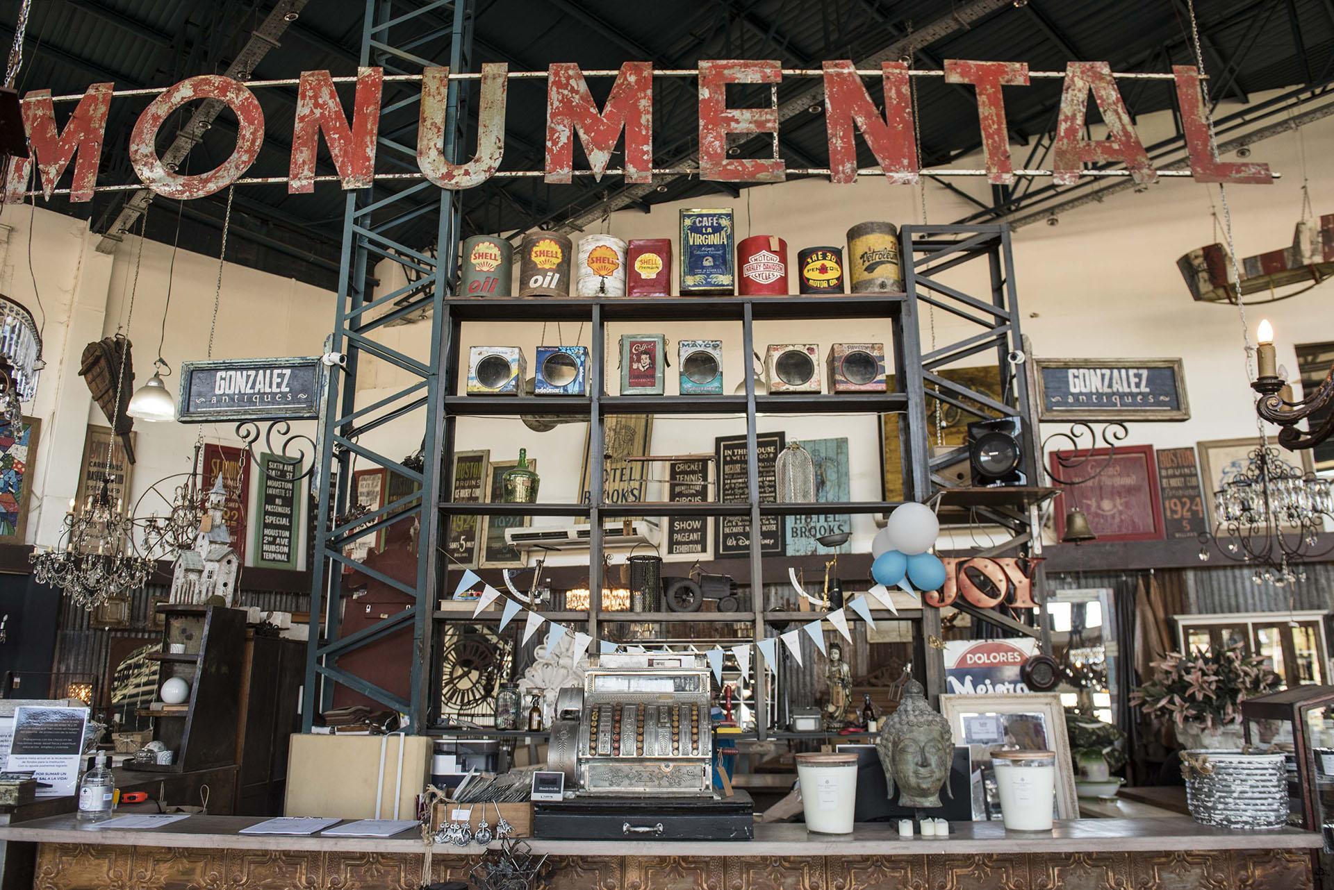 """""""Monumental"""", dice el cartel en el frente de donde se encuentra la caja está lleno de objetos de decoración antiguo como tachos de gasolina de diferentes marcas"""