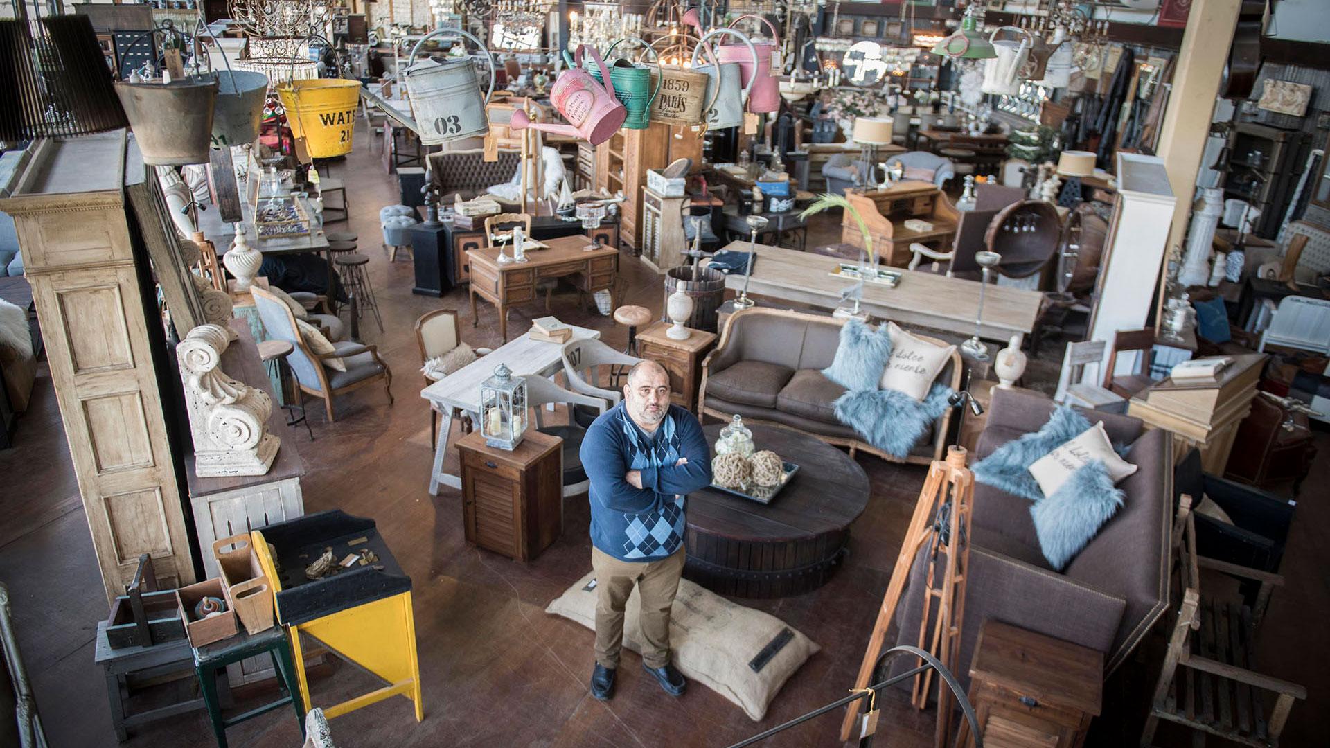 Diego González, uno de los dueños de Antigüedades González, en la planta baja de su tienda. Sillones, regaderas colgando del techo, almohadones de peluche, juegos antiguos y esculturas se pueden ver a lo largo y a lo ancho del anticuario