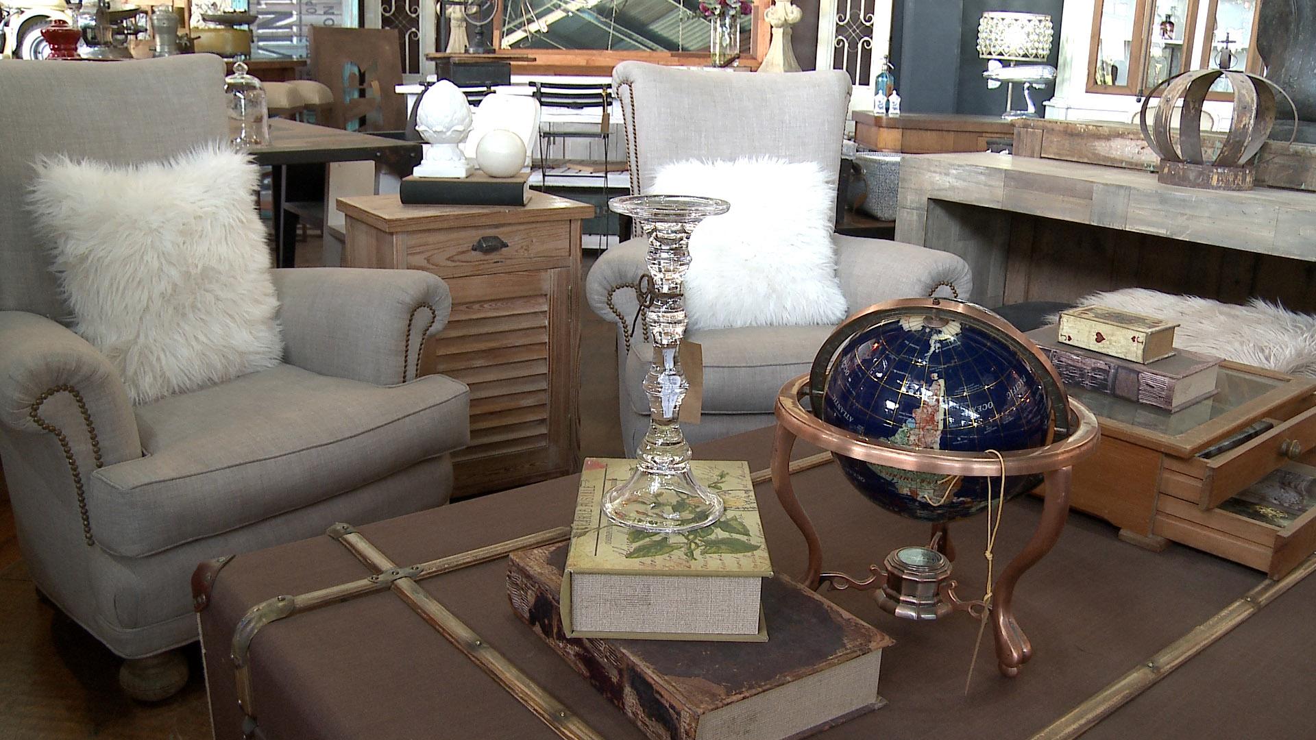 Valijas gigantes como mesas ratonas, muebles de estilo con sillones vintage, candelabros y objetos de decoración pequeños. Una imagen de un living de diseño que mezcla lo antiguo con lo moderno