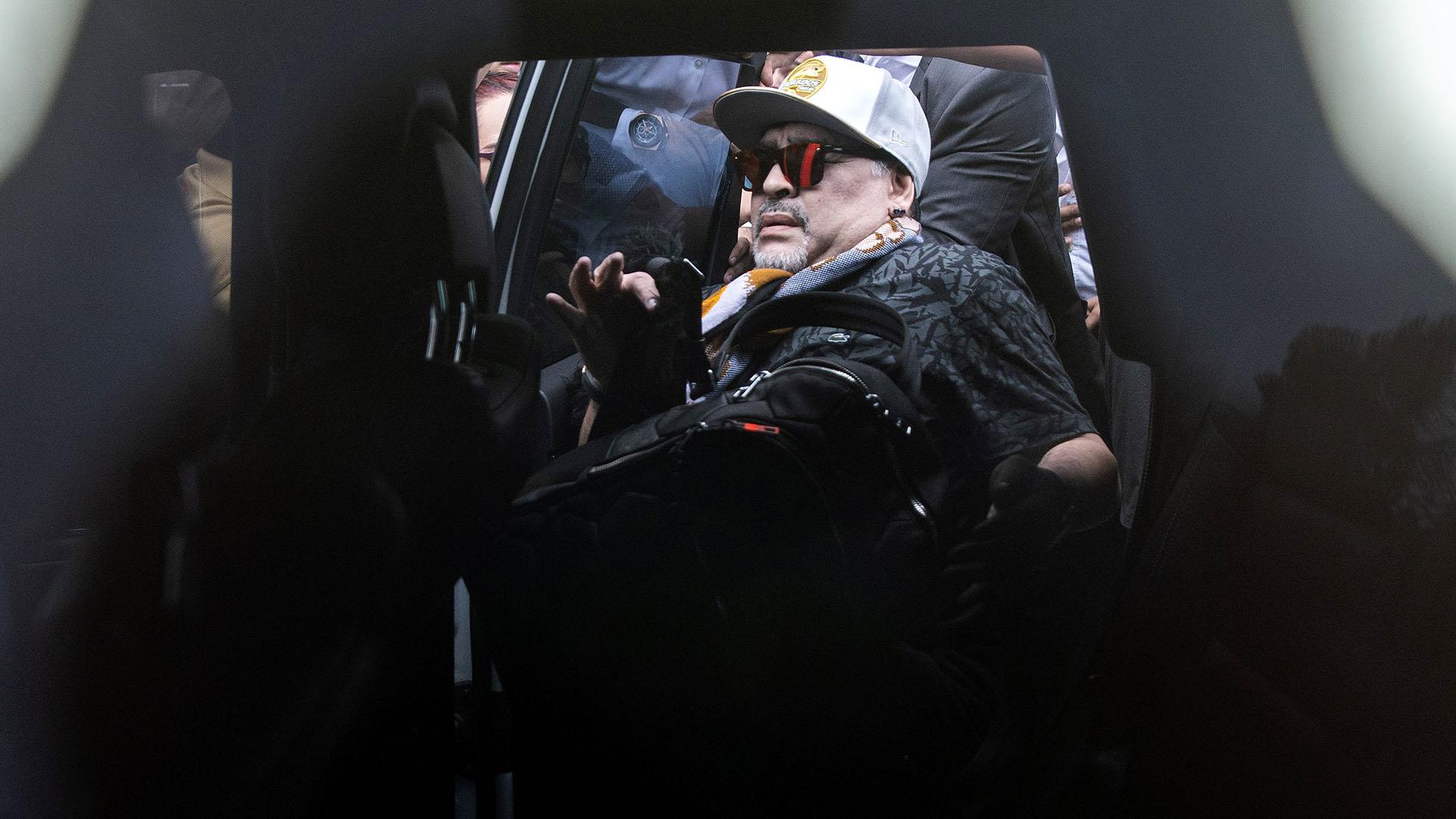 Diego Maradona ingresa a un automóvil a su llegada al aeropuerto internacional de Culiacán, estado de Sinaloa, México. Fue rodeado por cientos de fanáticos (AFP)