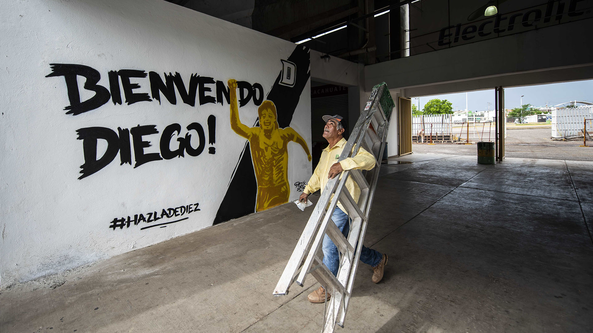 """Un trabajador caminafrente al mural del estadio de los Dorados de Sinaloa que reza: """"¡Bienvenido Diego!"""", recientemente graficado para esperar que el ex futbolista argentino sea presentado como nuevo entrenador del equipo, este lunesen Culiacán , Estado de Sinaloa, México (AFP)"""