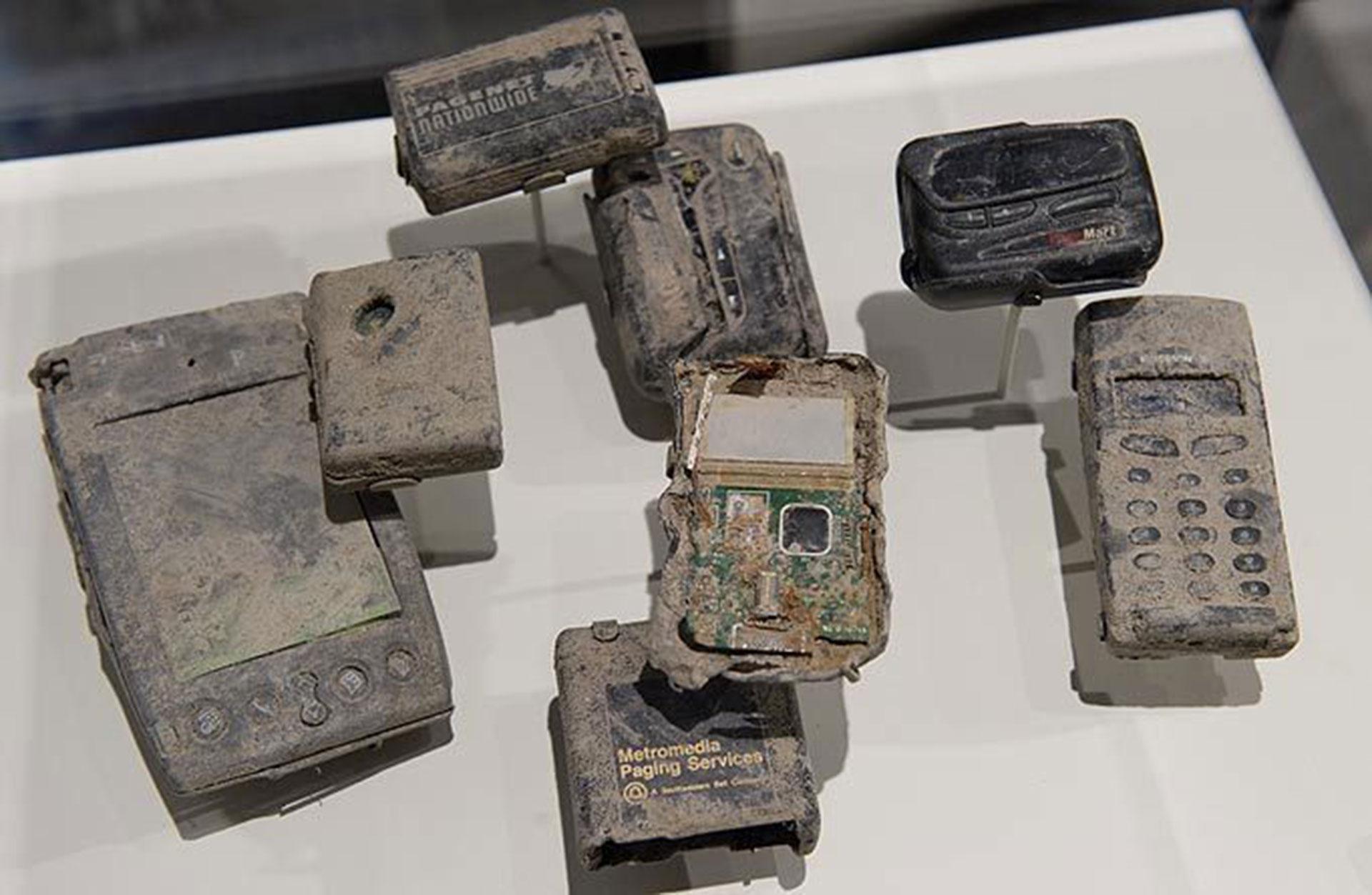Teléfonos celulares, localizadores y dispositivos Palm Pilot calcinados y cubiertos de polvo