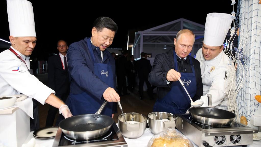 El presidente ruso Vladimir Putin y el presidente chino Xi Jinping hacen panqueques durante una visita a la exposición de la calle Lejano Oriente al margen del Foro Económico del Este en Vladivostok, Rusia, el 11 de septiembre de 2018. Sergei Bobylev/TASS Agencia de Fotografía/Piscina vía REUTERS (Reuters)