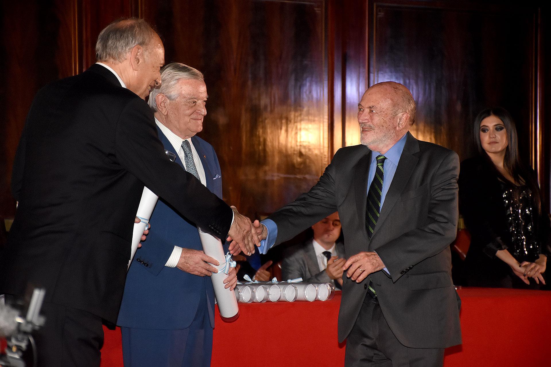 El empresario Alberto Grimoldi saluda a Luis Ovsejevich junto a Juan Carlos Bagó