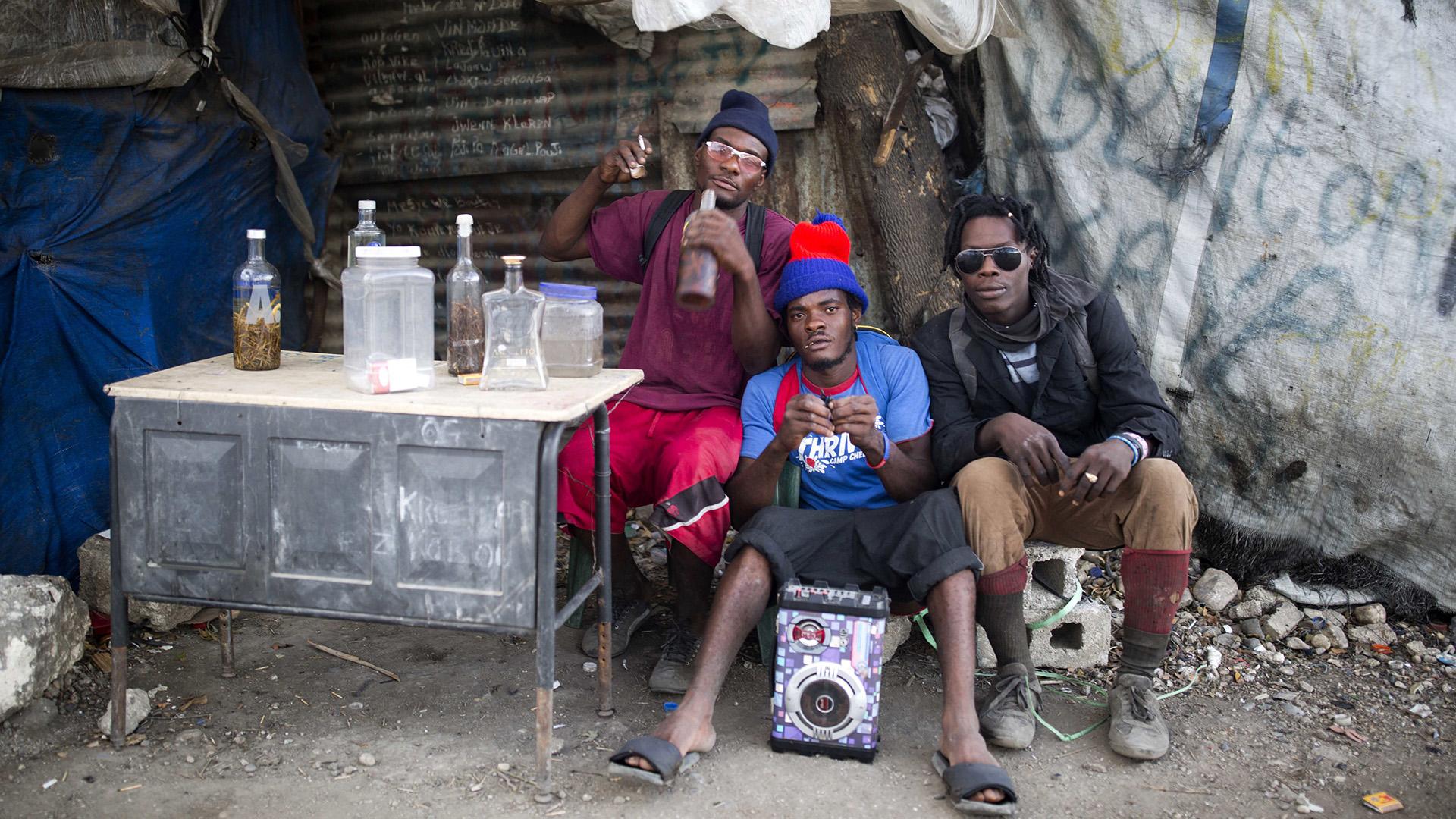 Tres hombres sentados tomando un refresco en el basurero (AP)