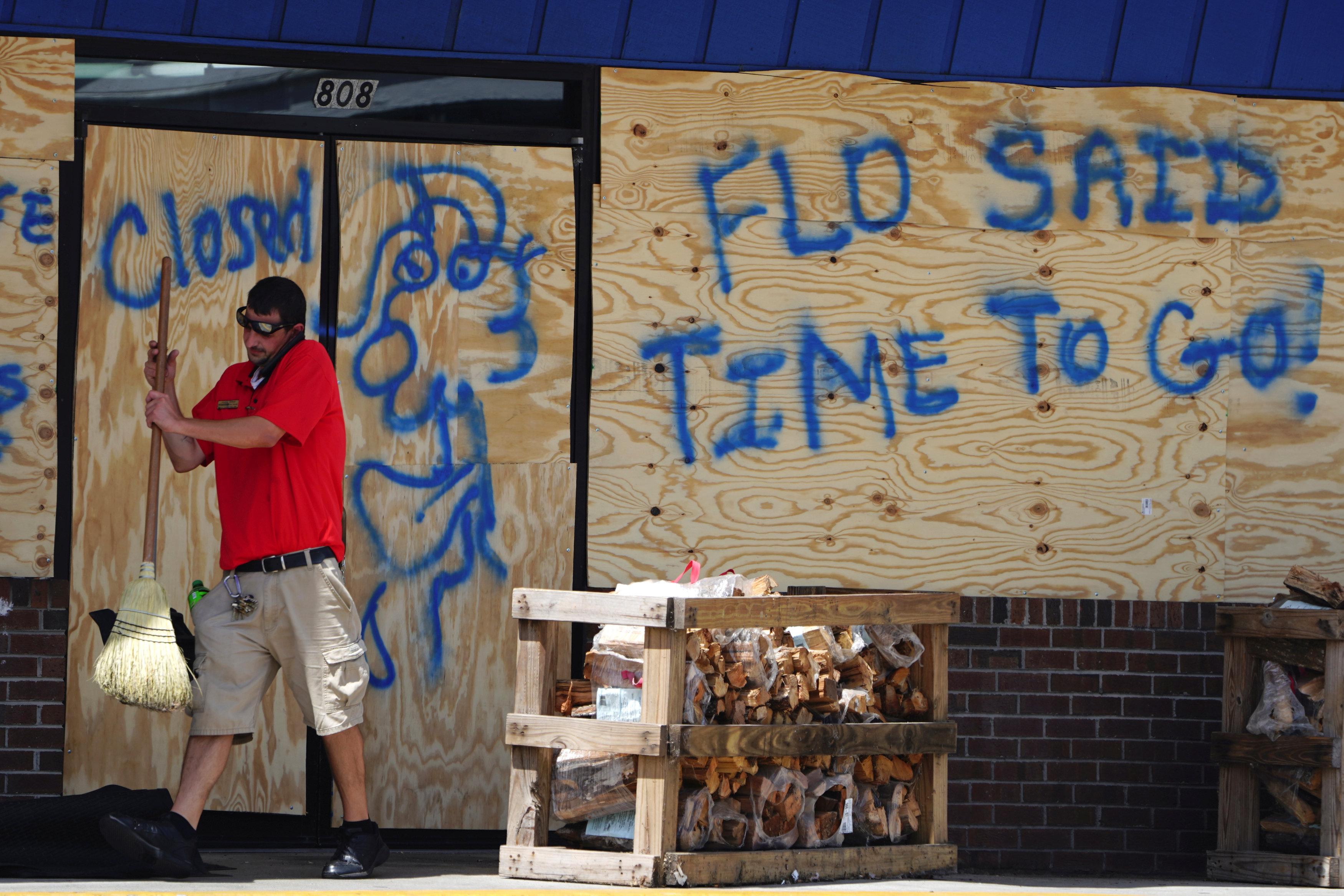 """""""Flo dijo 'es hora deirse!'"""", resalta un mensaje sobre un comercio de Carolina Beach, junto a un dibujo"""