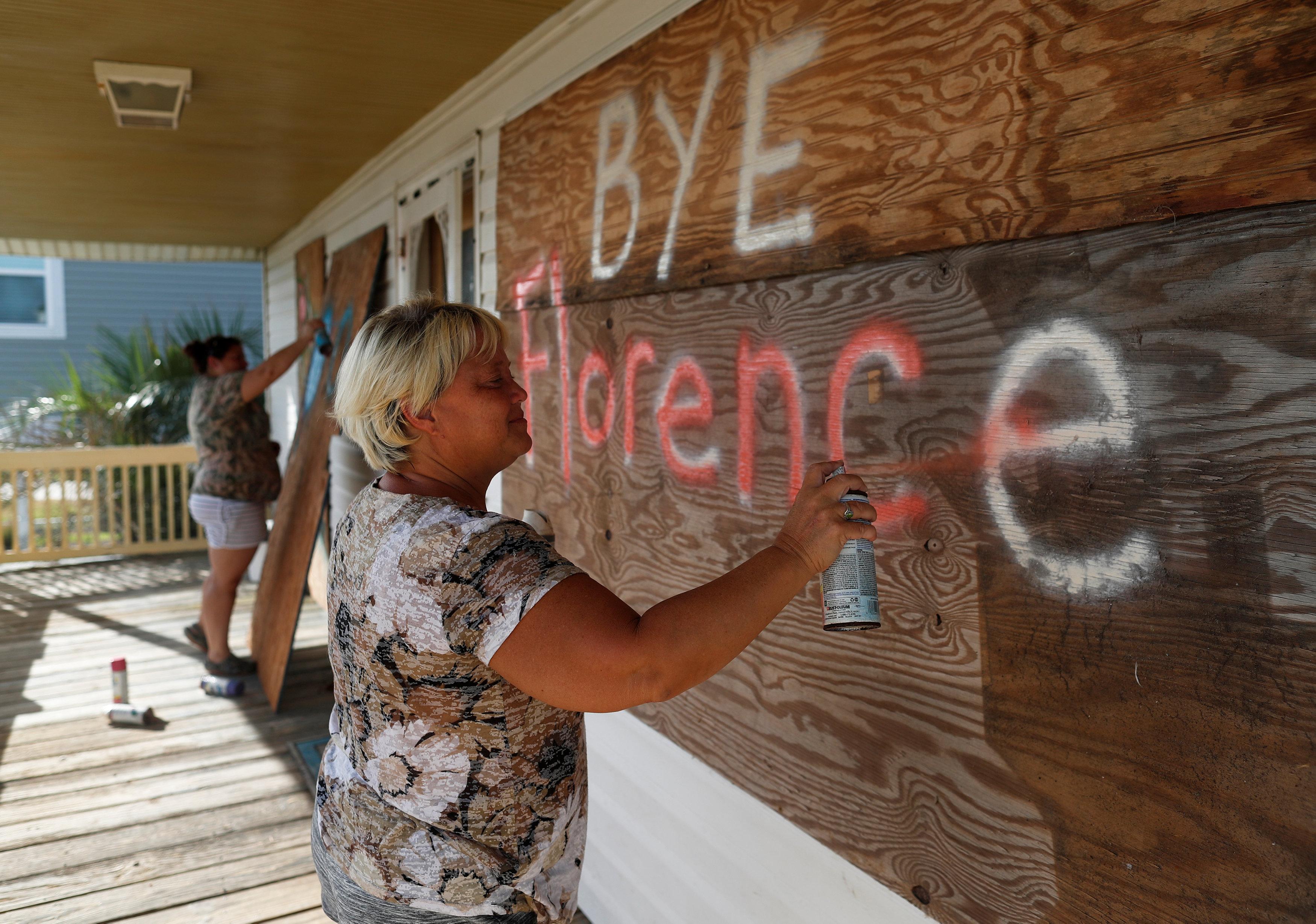 """""""Adiós, Florence"""". Lisa Evers y su hija Amanda Hamilton, de Oak Island, decoran las tablas con las que protegieron su hogar como último paso antes de evacuar"""