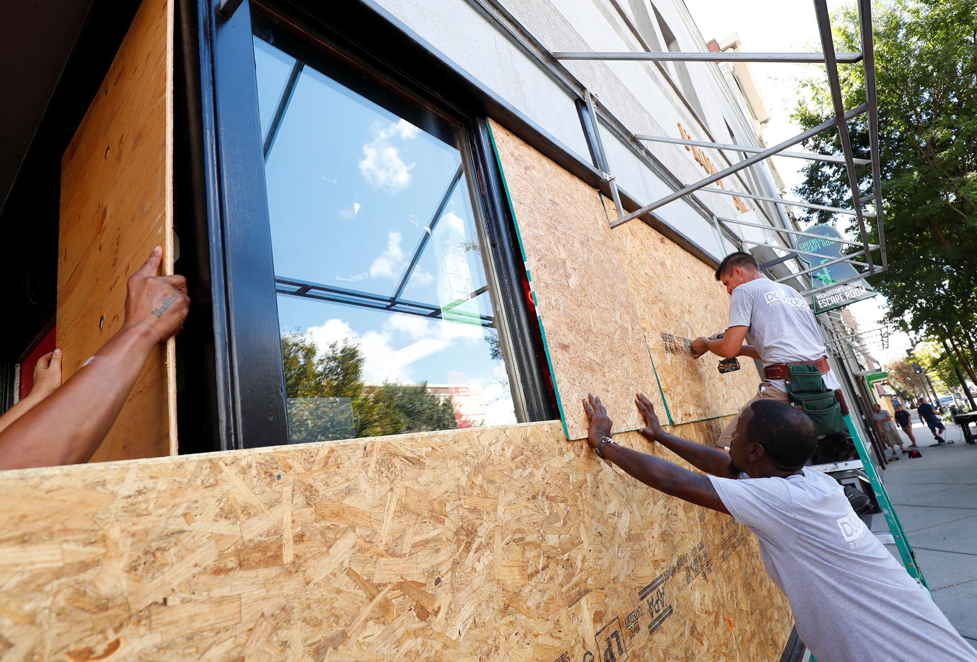 Trabajadores aseguran la madera para proteger ventanales antes de la llegada del huracán Florence en Wilmington, Carolina del Norte, EE.UU, 12 de septiembre de 2018 (REUTERS / Chris Keane)