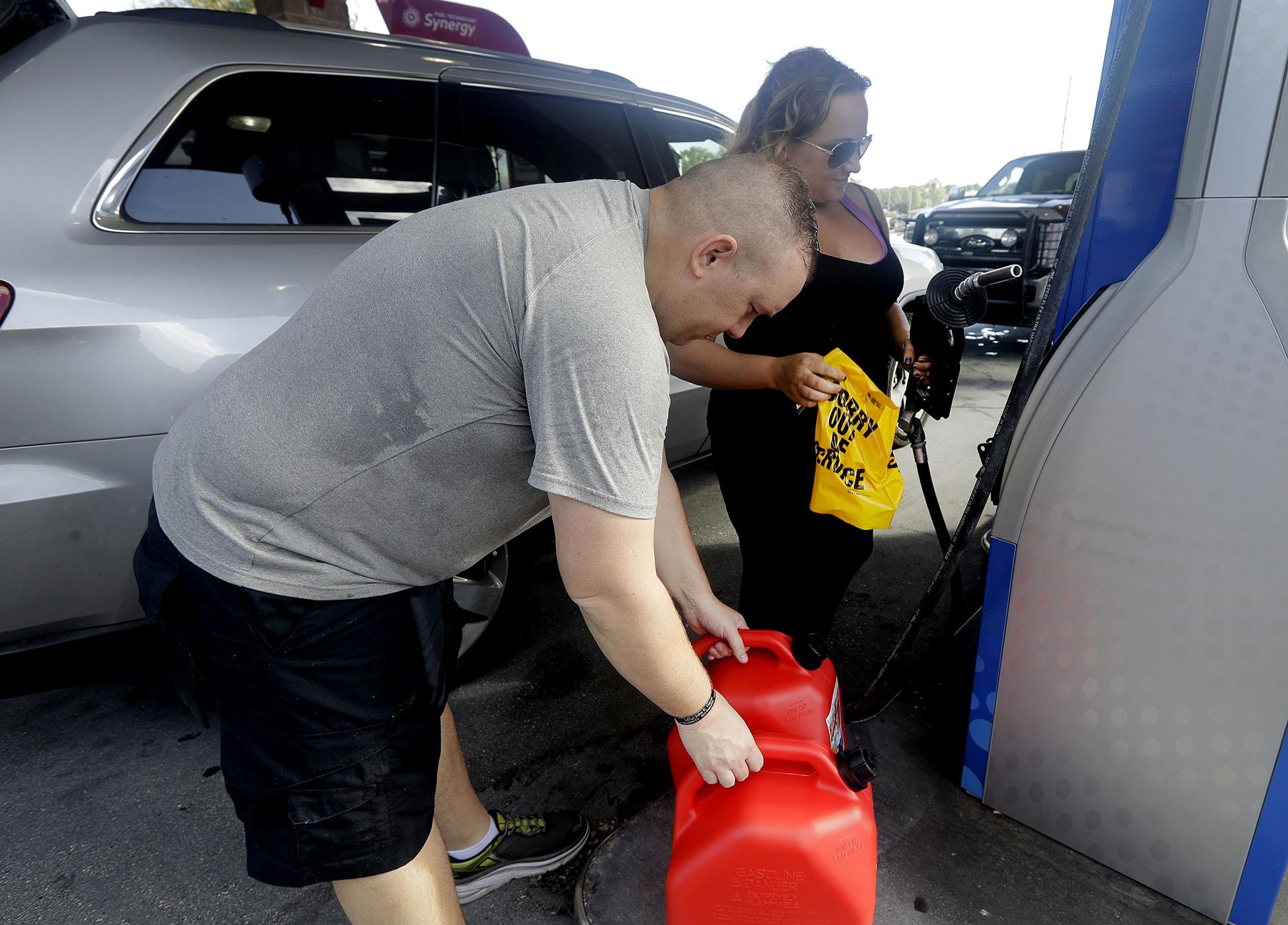 """Sarah Dankanich saca un envoltorio """"fuera de servicio"""" de una bomba de gasolina mientras su esposo, Bryan Dankanich, se prepara paracargar gasolina en latas antes del huracán Florence en Wilmington, Carolina del Norte (AP Photo/Chuck Burton)"""