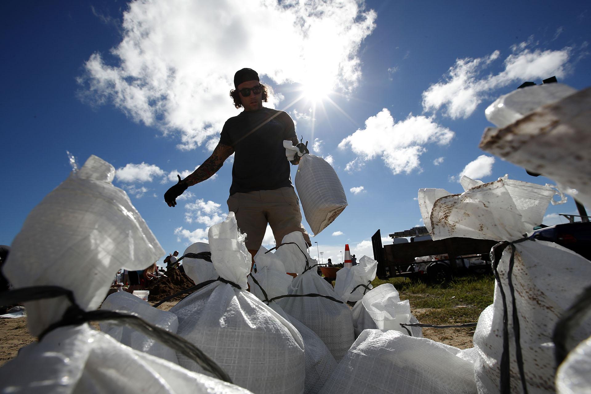 Un residente de Virginia Beach, Virginia,carga un saco de arena antes dellevarlo a su camioneta (AP Photo/Alex Brandon)