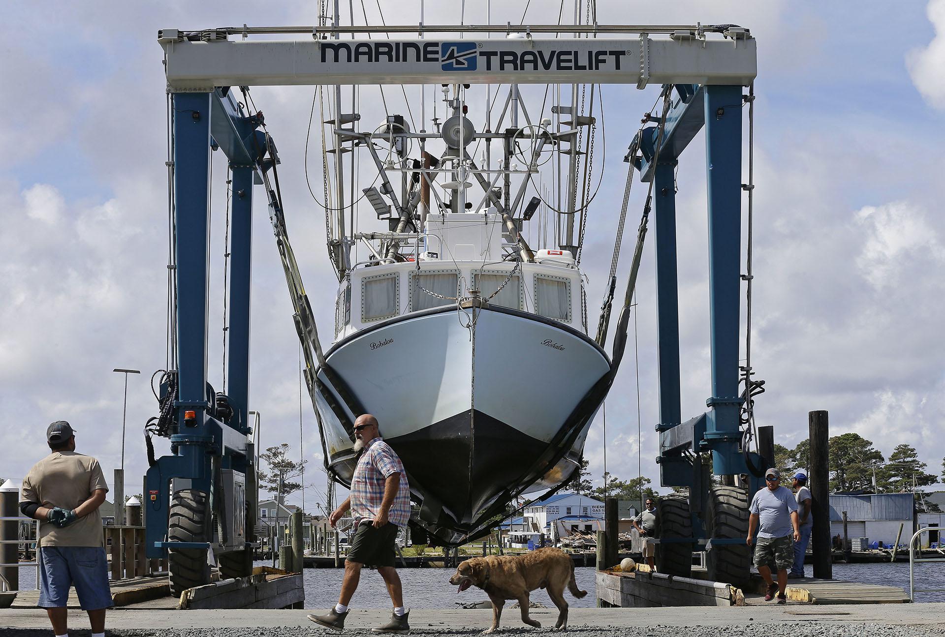 Los trabajadoressacan barcos fuera del agua en el puerto de Wanchese, Carolina del Norte (AP Photo/Gerry Broome)