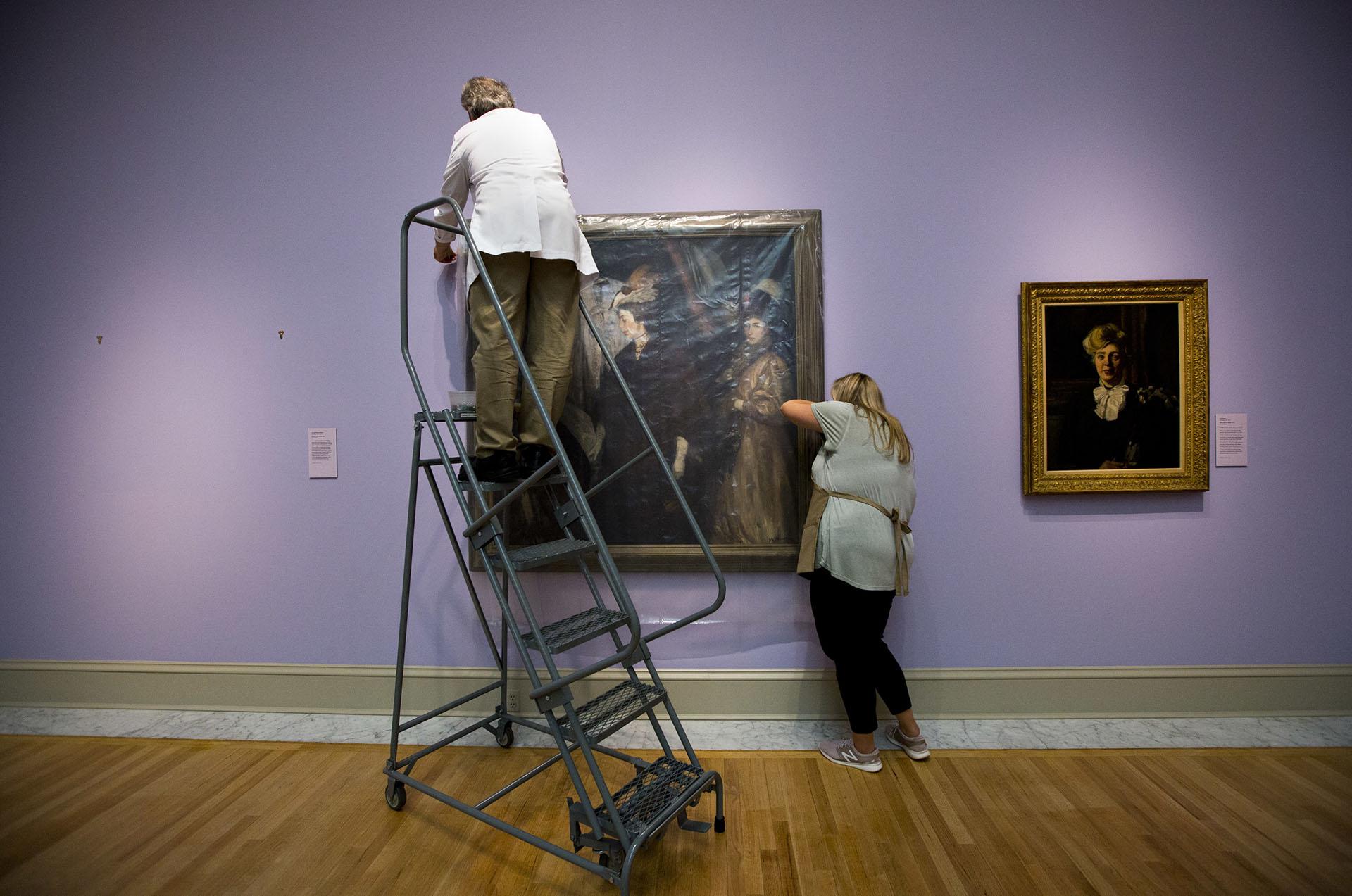 """Mark Lewis, conservador, y Alisa Reynolds aseguran el cuadro """"The Shoppers"""" de William James Glackens en el Museo de Arte Chrysler (The' N. Pham/The Virginian-Pilot via AP)"""