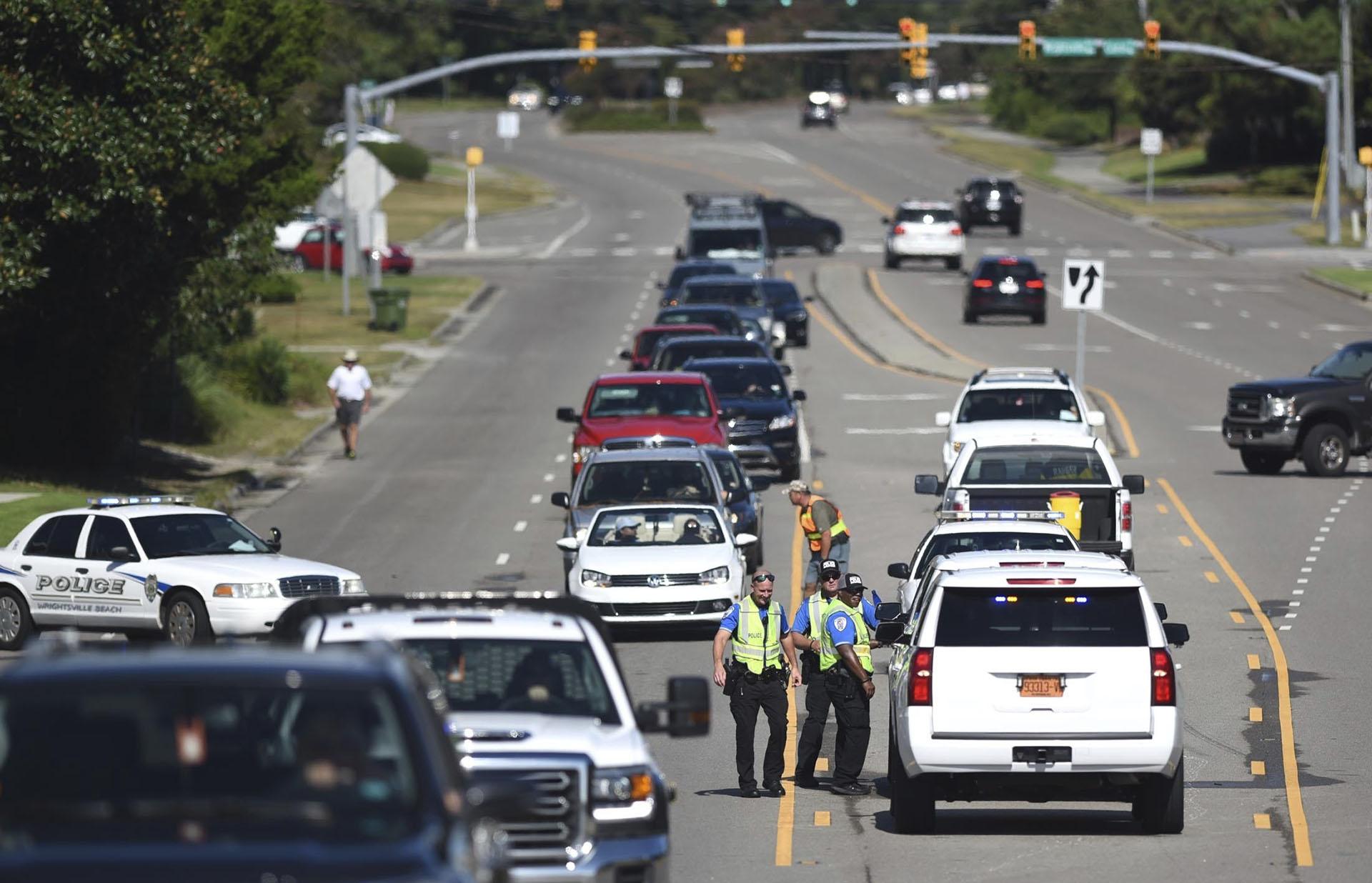 Los policías de Wrightsville Beach comprueban la identificación en el puente a Wrightsville Beach. Miles de personastratande huir del paso del huracán (Matt Born/The Star-News via AP)