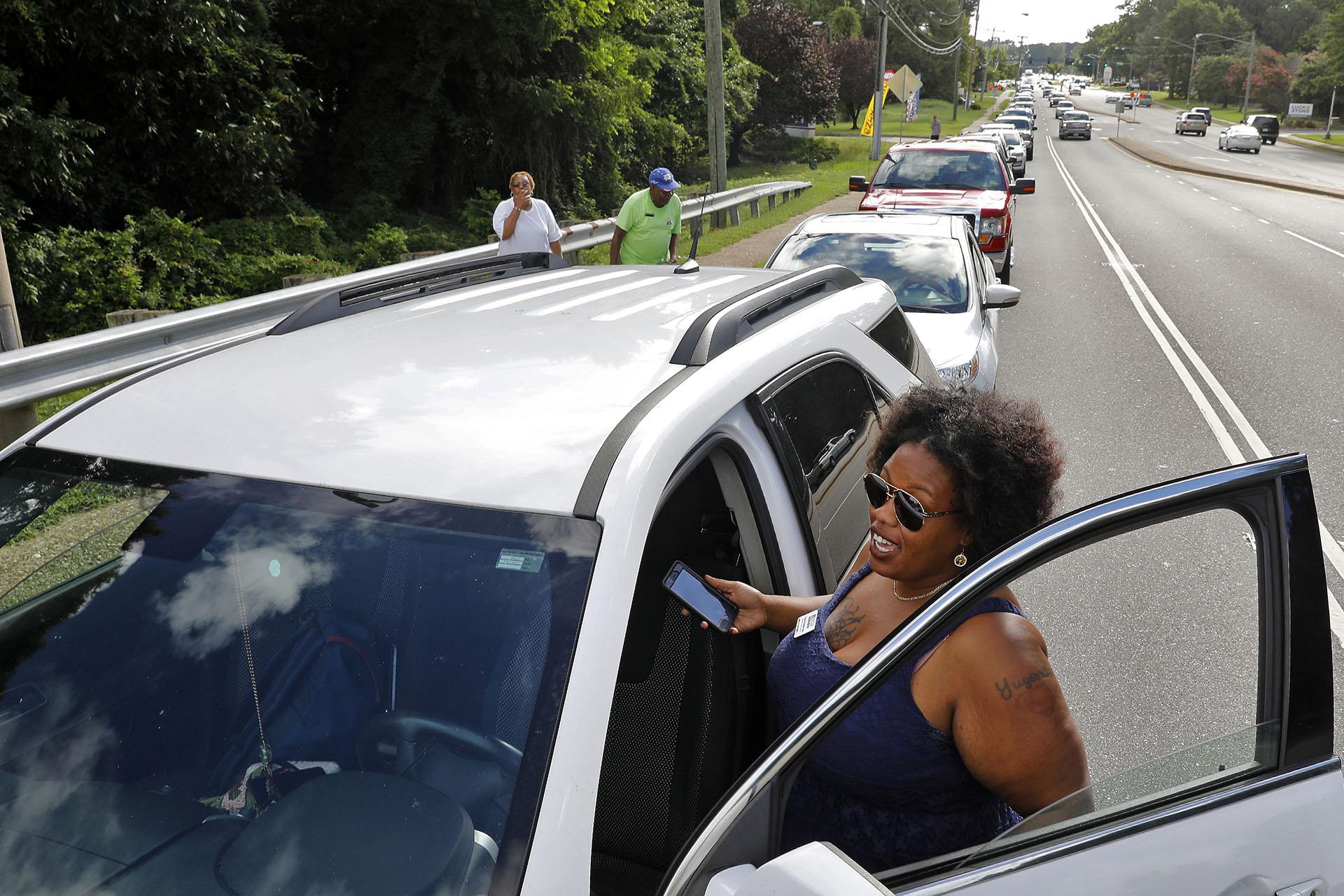 Yugonda Sample espera fuera de su automóvil en una fila de autos a lo largo de Oyster Point Road mientras la genteespera recoger sacos de arena. La ciudad de Newport News ofrecía sacos de arena gratis a los residentes en el Centro de Operaciones de Obras Públicas a medida que se aproxima el huracán Florence (Jonathon Gruenke/The Daily Press via AP)