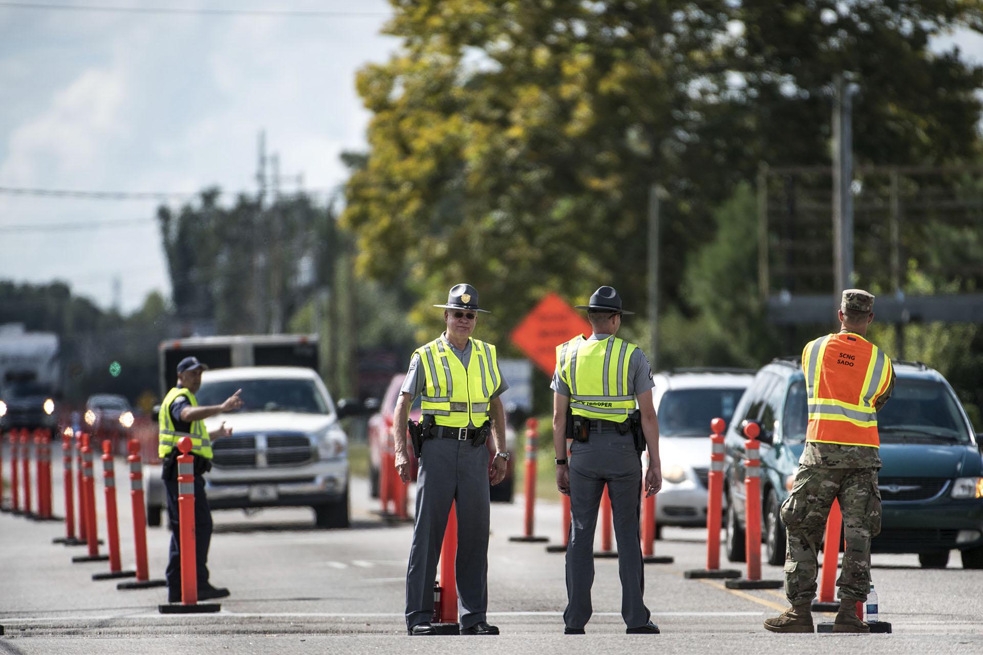 Los miembros de las fuerzas del orden trabajan con la Guardia Nacional para dirigir el tráfico hacia la autopista US 501 mientras el huracán Florence se acerca a la costa este (AP Photo/Sean Rayford)