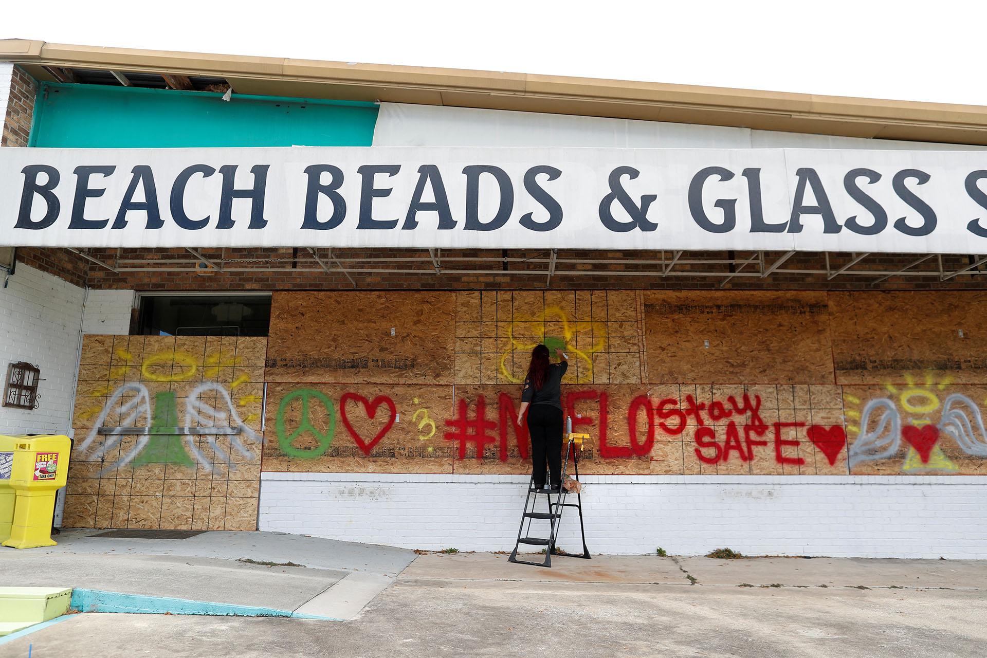 Heather Samson, dueña de Beach Beads and Glass Studio, usa pintura en aerosol para dejar mensajes en su negocio antes de la llegada del huracán Florence en Surfside Beach, Carolina del Sur (REUTERS/Randall Hill)