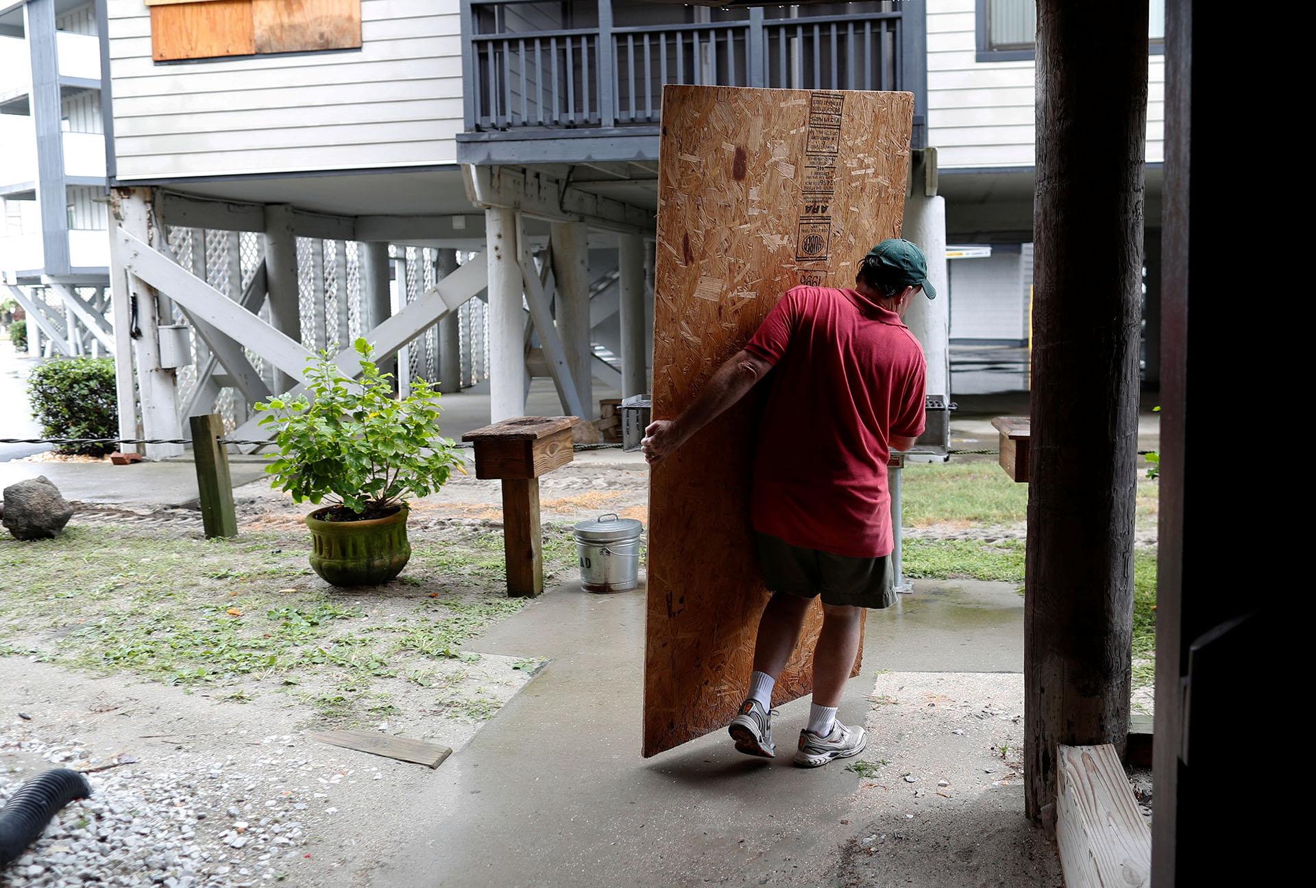 John Muchmore ayuda a cargar maderas para protegerlos condominios Afterdeck antes de la llegada del huracán Florence en Garden City Beach, Carolina del Sur (REUTERS/Randall Hill)