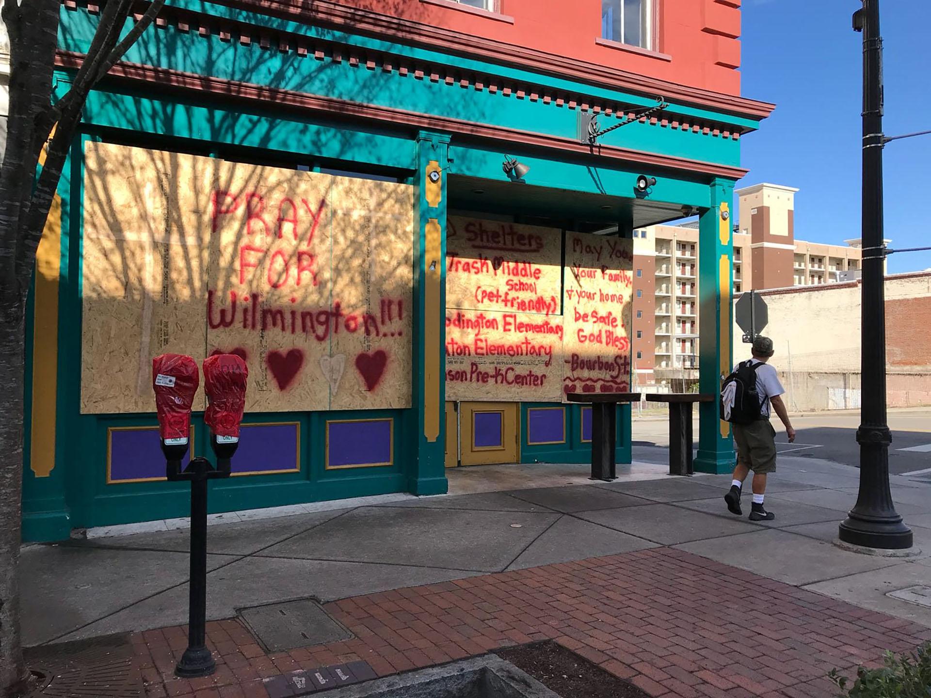 """Un hombrelee un graffiti que dice """"Rezapor Wilmington"""" en un negociocerrado por la llegada del huracán Florence en Wilmington, Carolina del Norte, Estados Unidos (REUTERS/Ernest Scheyder)"""