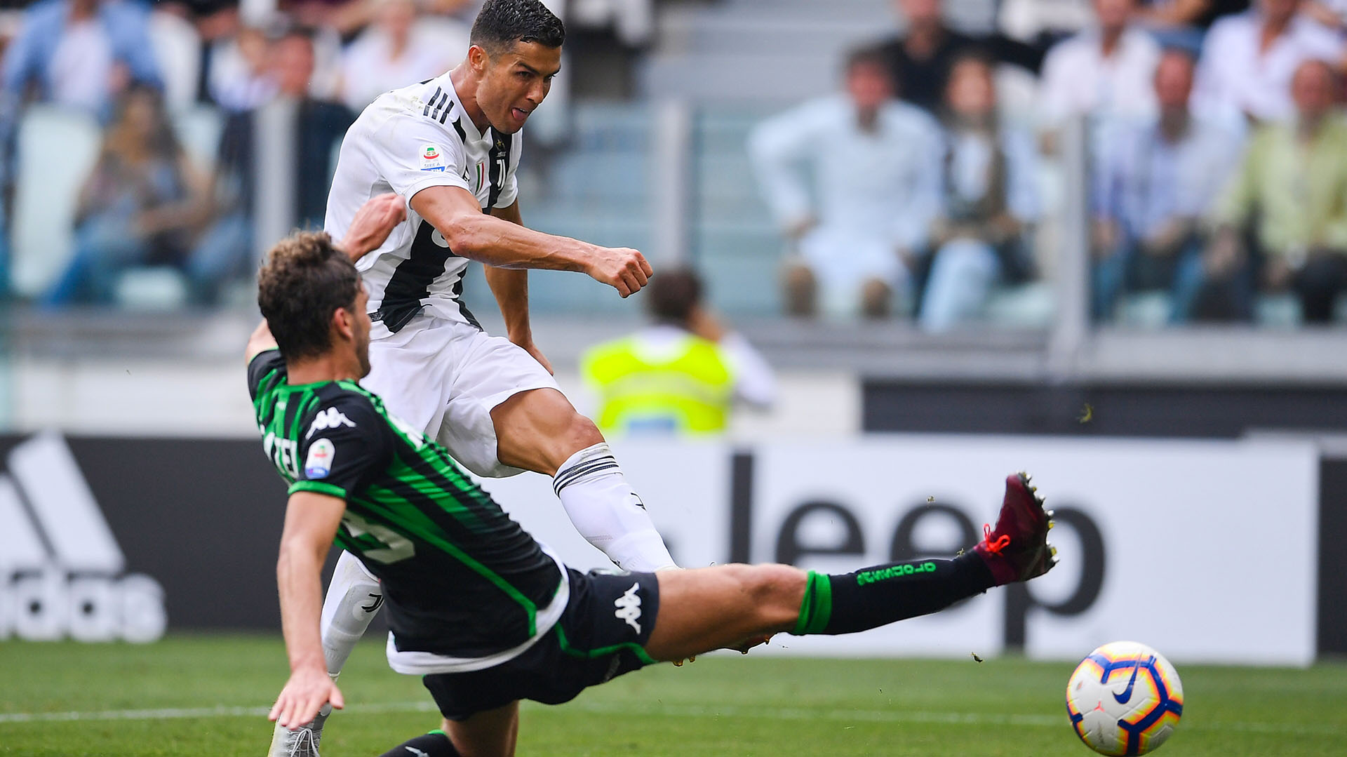 Juventus' Portuguese forward Cristiano Ronaldo shoots to score his second goal during the Italian Serie A football match Juventus vs Sassuolo on September 16, 2018 at the Juventus stadium in Turin. / AFP PHOTO / Marco BERTORELLO