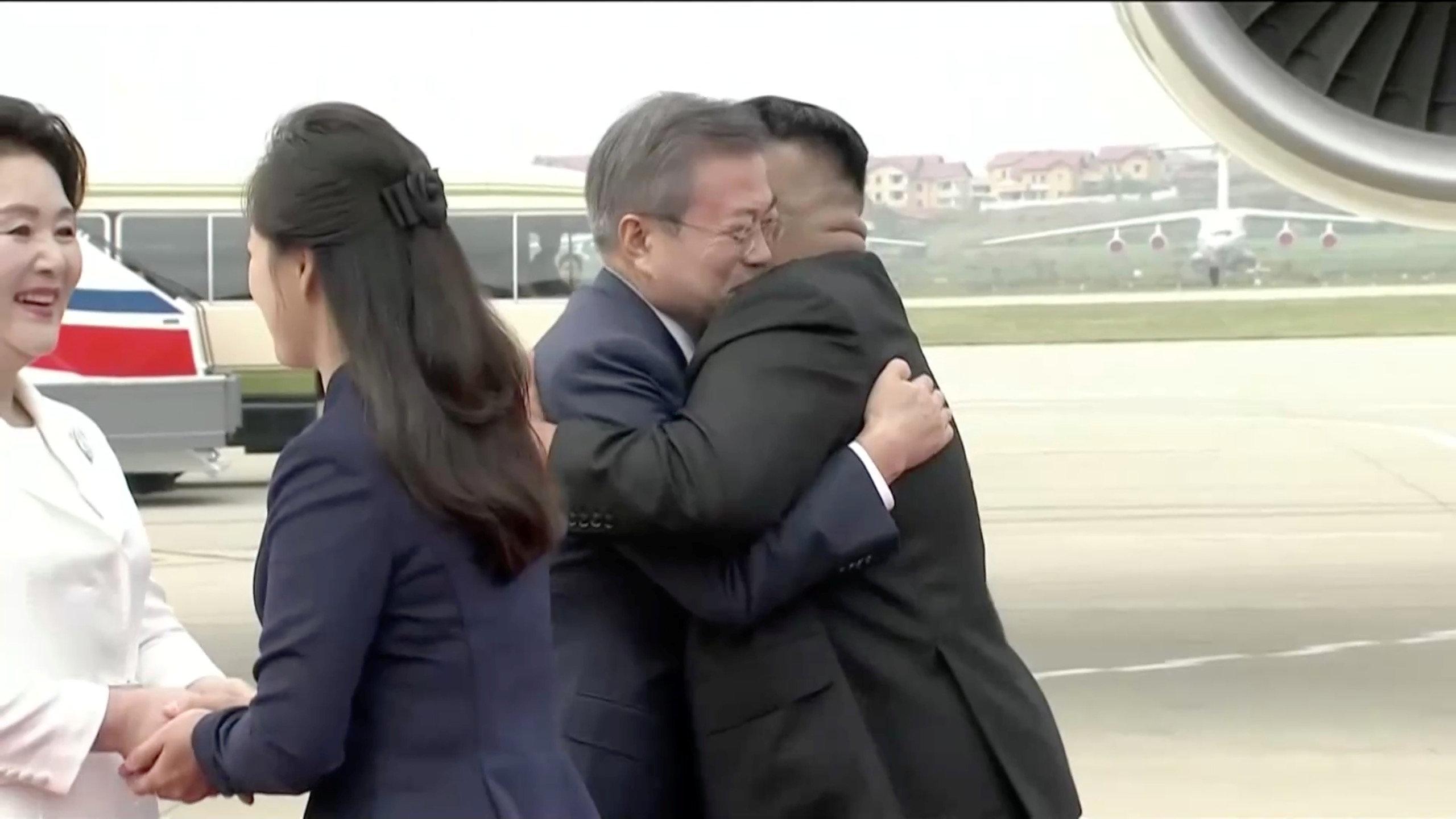Los dos dirigentes se abrazaron después de que Moon bajara del avión. Acompañados por sus esposas, bromearon durante unos minutos, mientras cientos de personas agitaban banderas norcoreanas y emblemas de la unificación