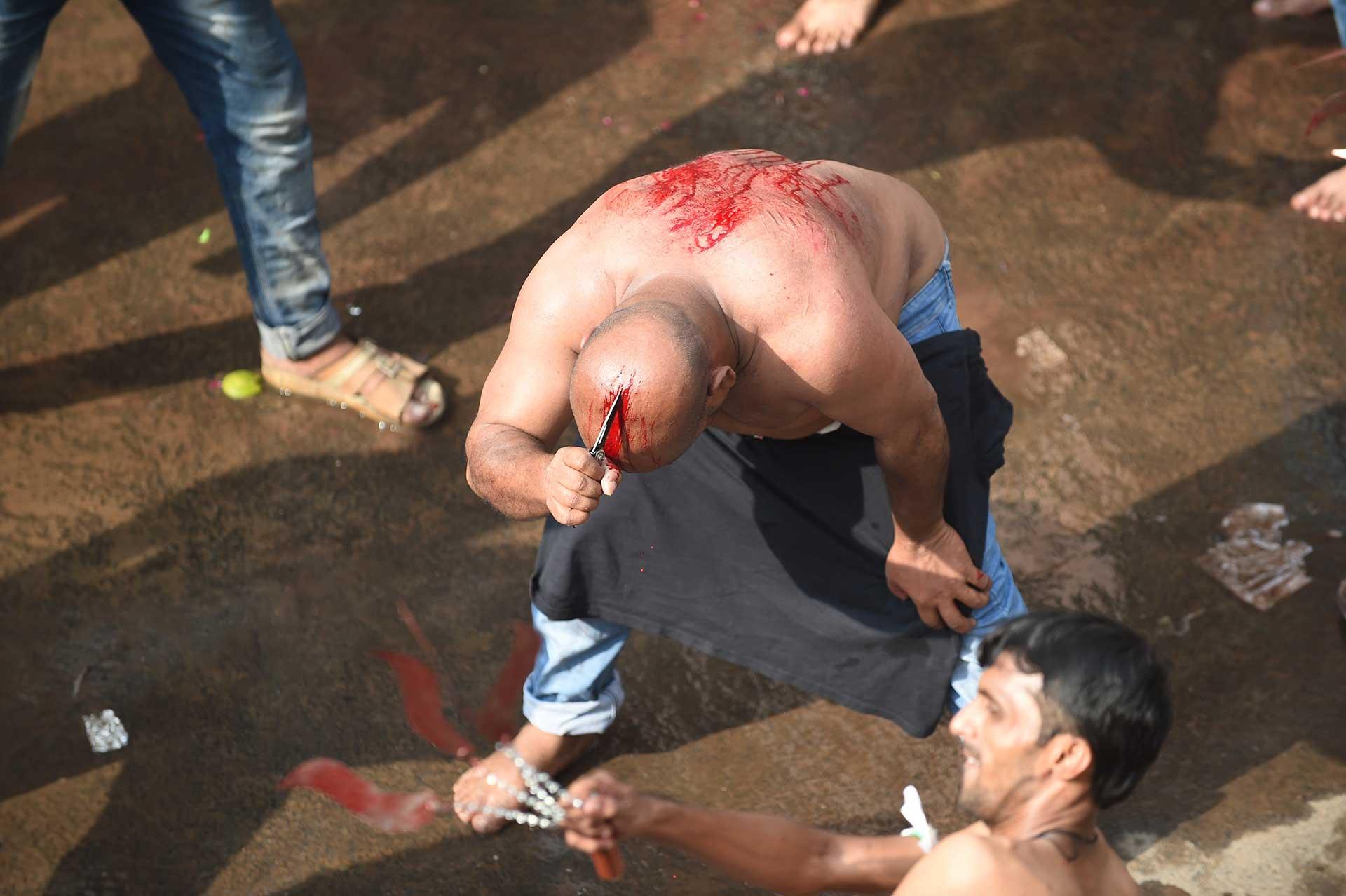 Durante el ritual es normal ver a hombres que se cortan las cabezas con cuchillos (AFP)