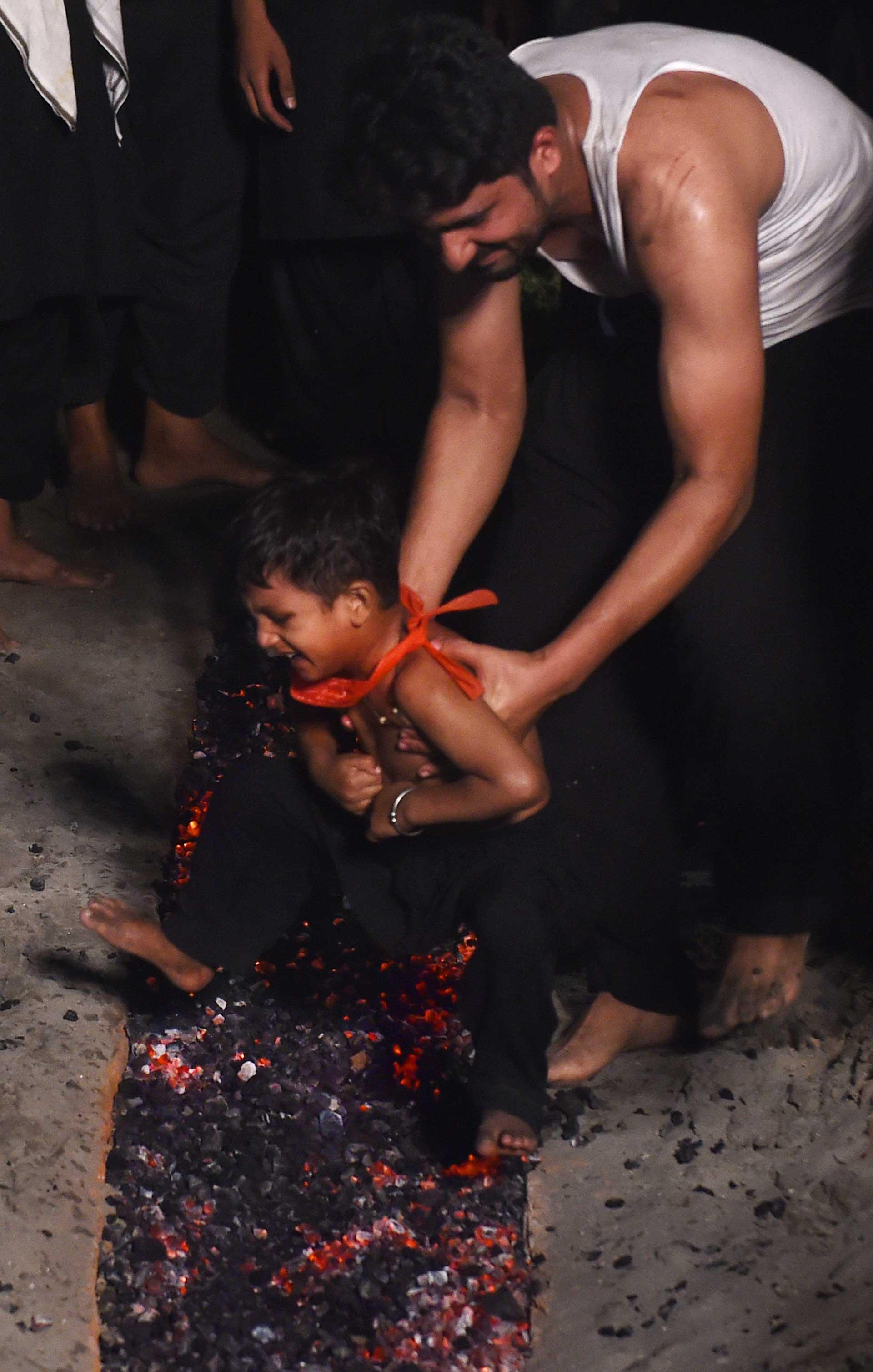 Pese al sufrimiento que refleja su rostro, el niño es obligado a caminar sobre las brasas (AFP)